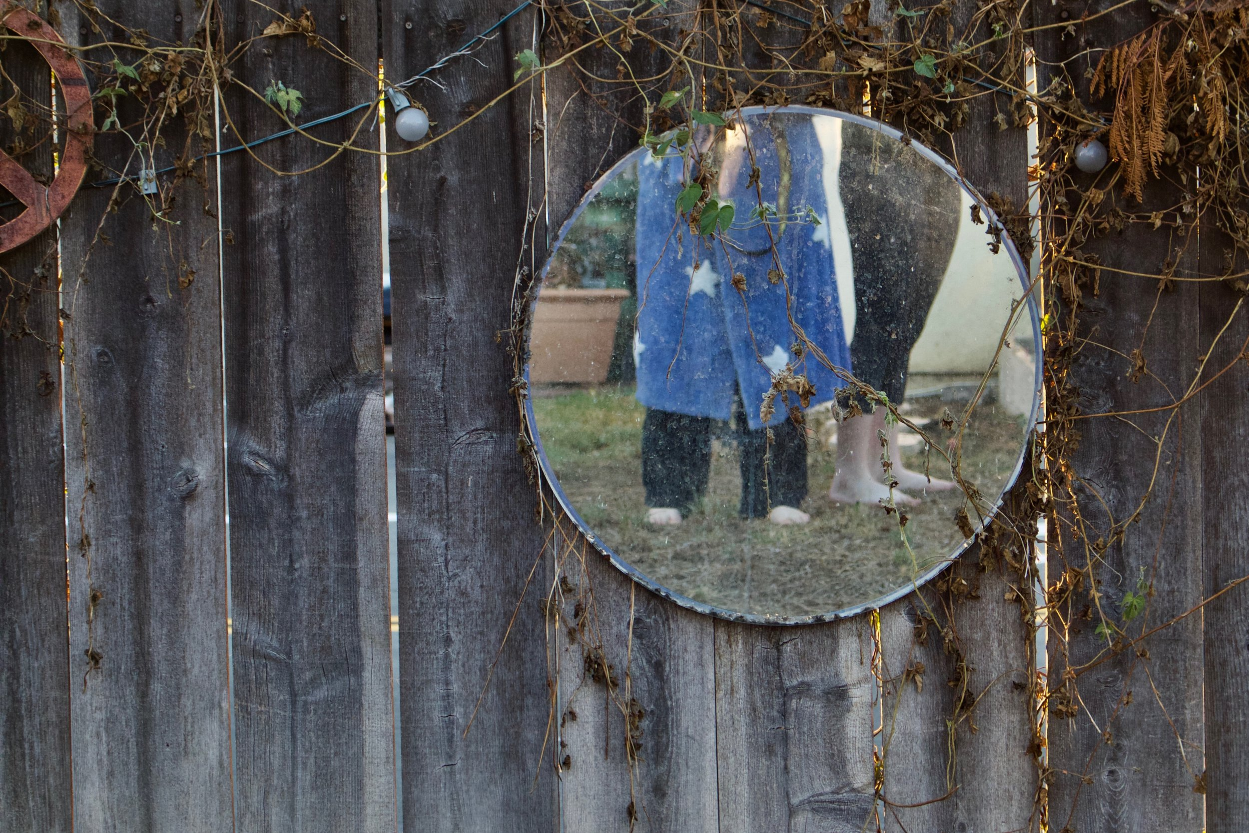 WE USED TO TAKE PICTURES IN THE MIRROR THAT ONCE HUNG ON THE FENCE THAT ONCE WAS THERE.