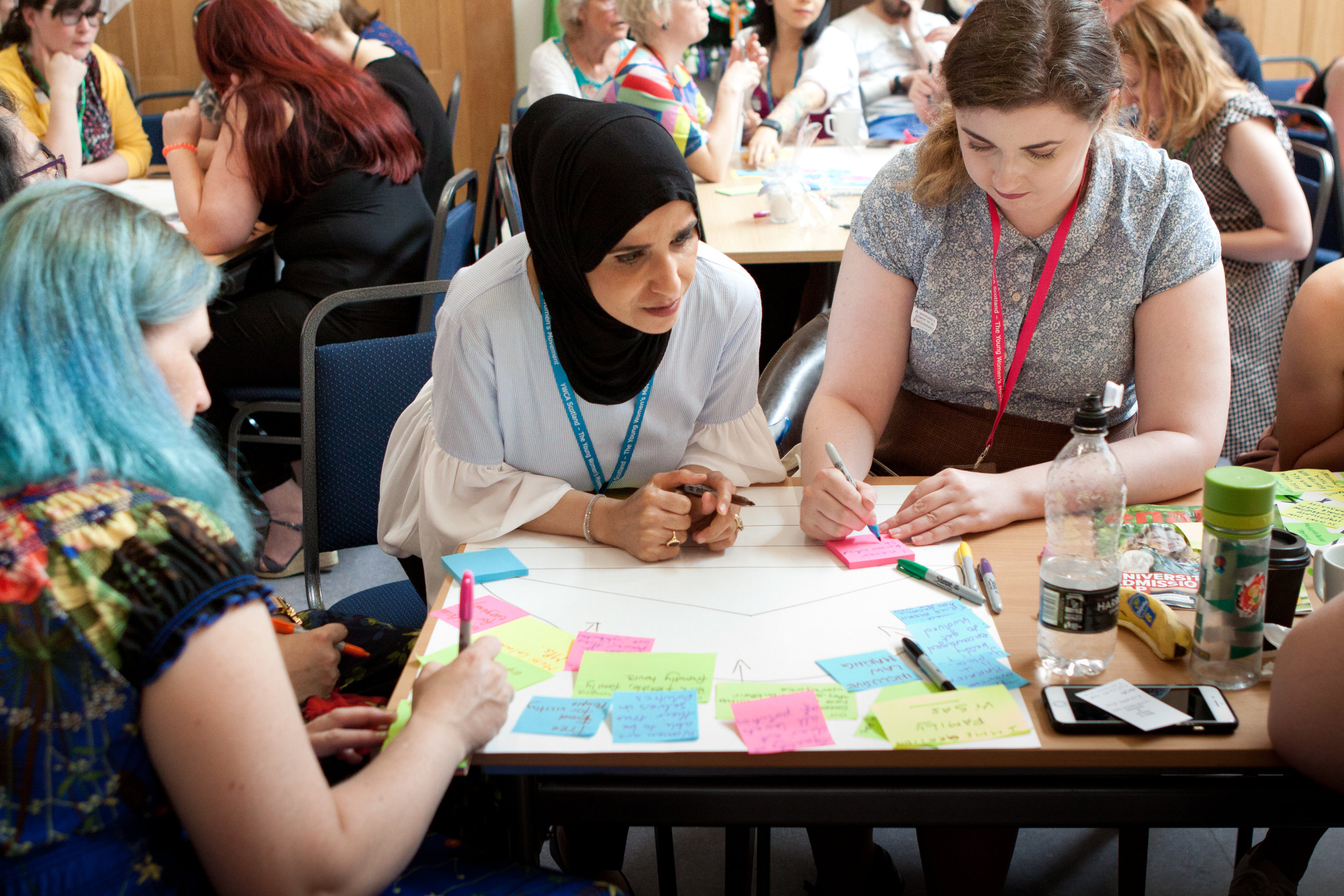 Three women strategise around a table with post-it notes at a Parliament Project event.