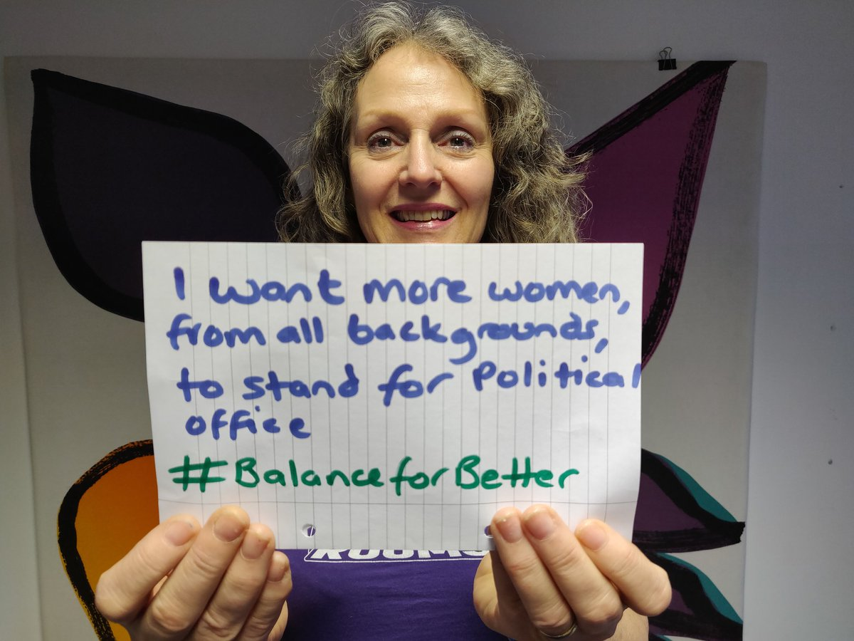 "Jane holds a piece of paper which reads ""I want more women, from all backgrounds, to stand for political office #BalanceForBetter."""