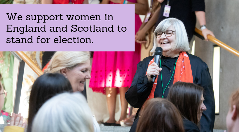 """A smiling woman speaks into a microphone at Scotland's Women Stand on the Garden Lobby steps, with the text """"We support women in England and Scotland to stand for election"""" in the foreground."""