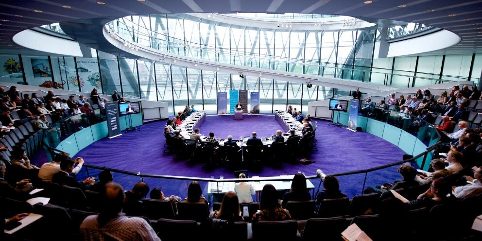 Image of the London Assembly, with members seated in a circle around the chamber.