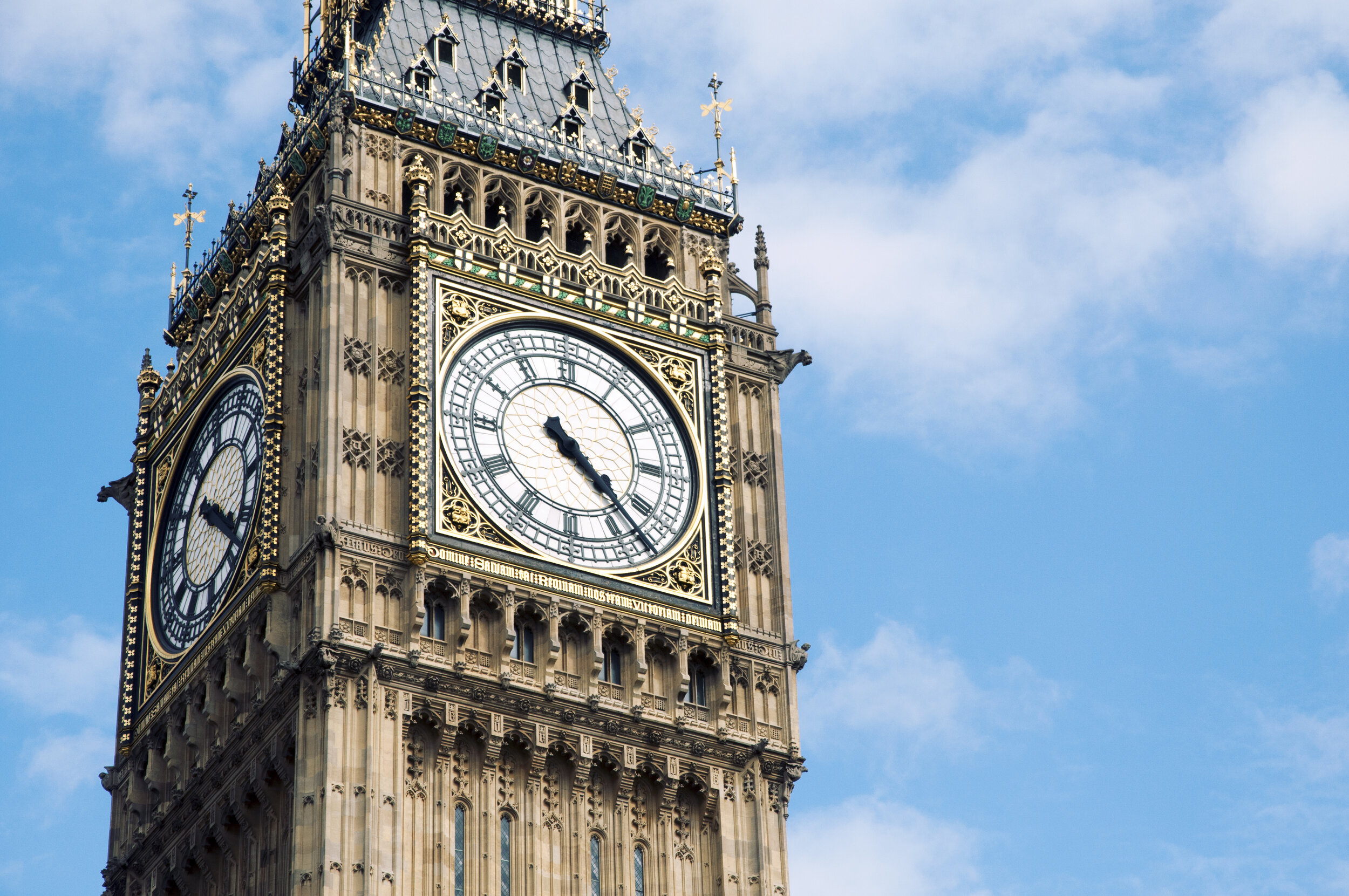 The top of Big Ben stands in front of a blue sky.