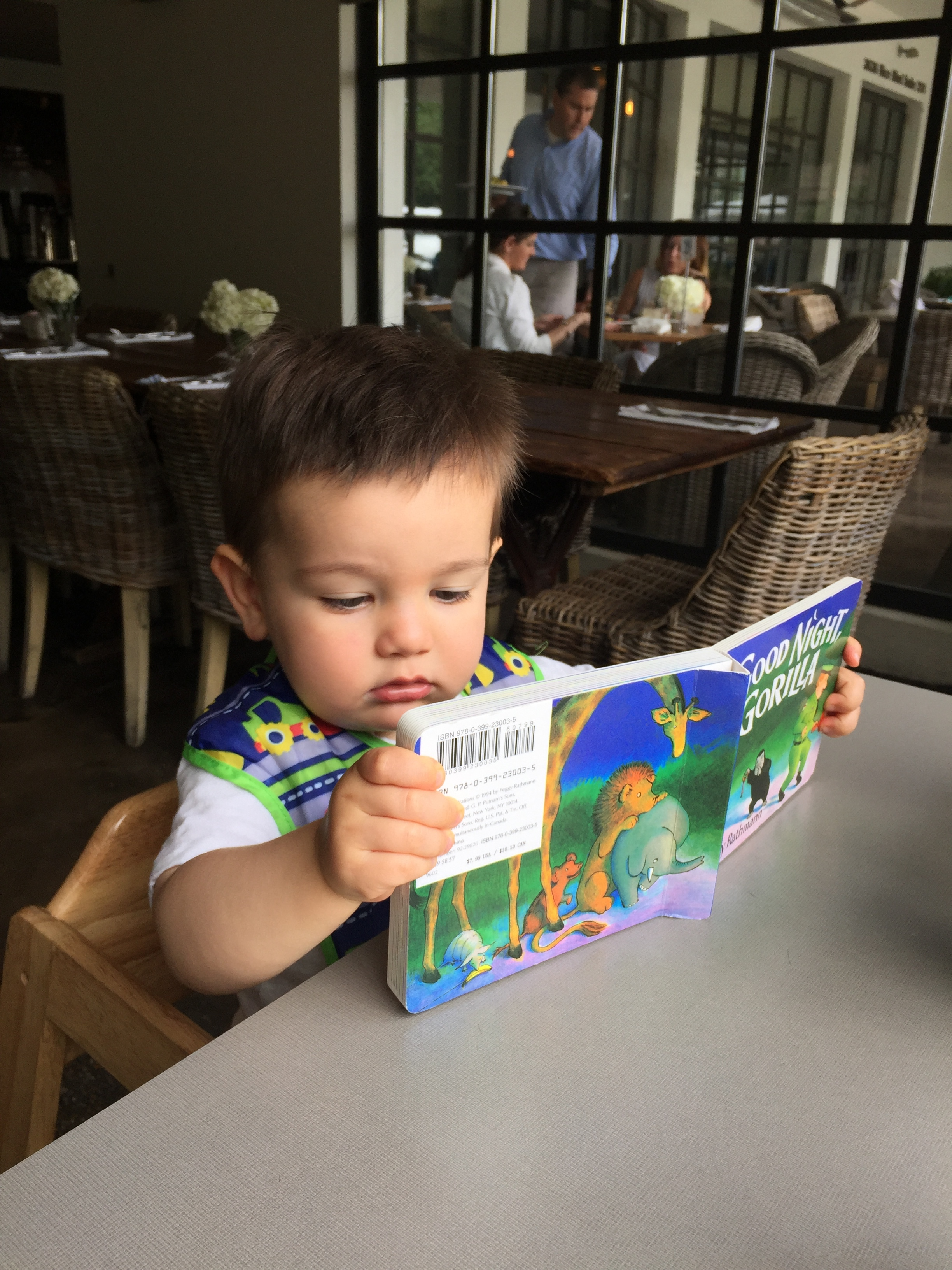 Keeping up on his reading during a lunch date with mom