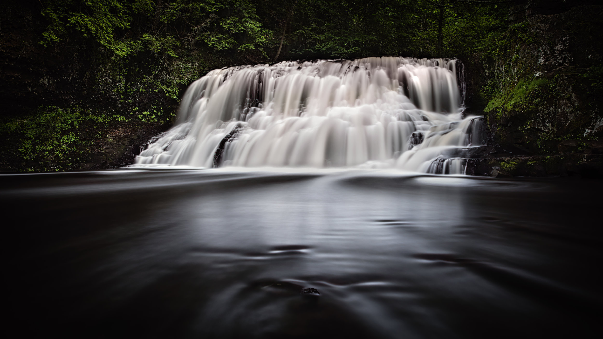 Head on, rocks in the middle with water going on either side of me. Trees blended in from a normal shutter speed for stillness.