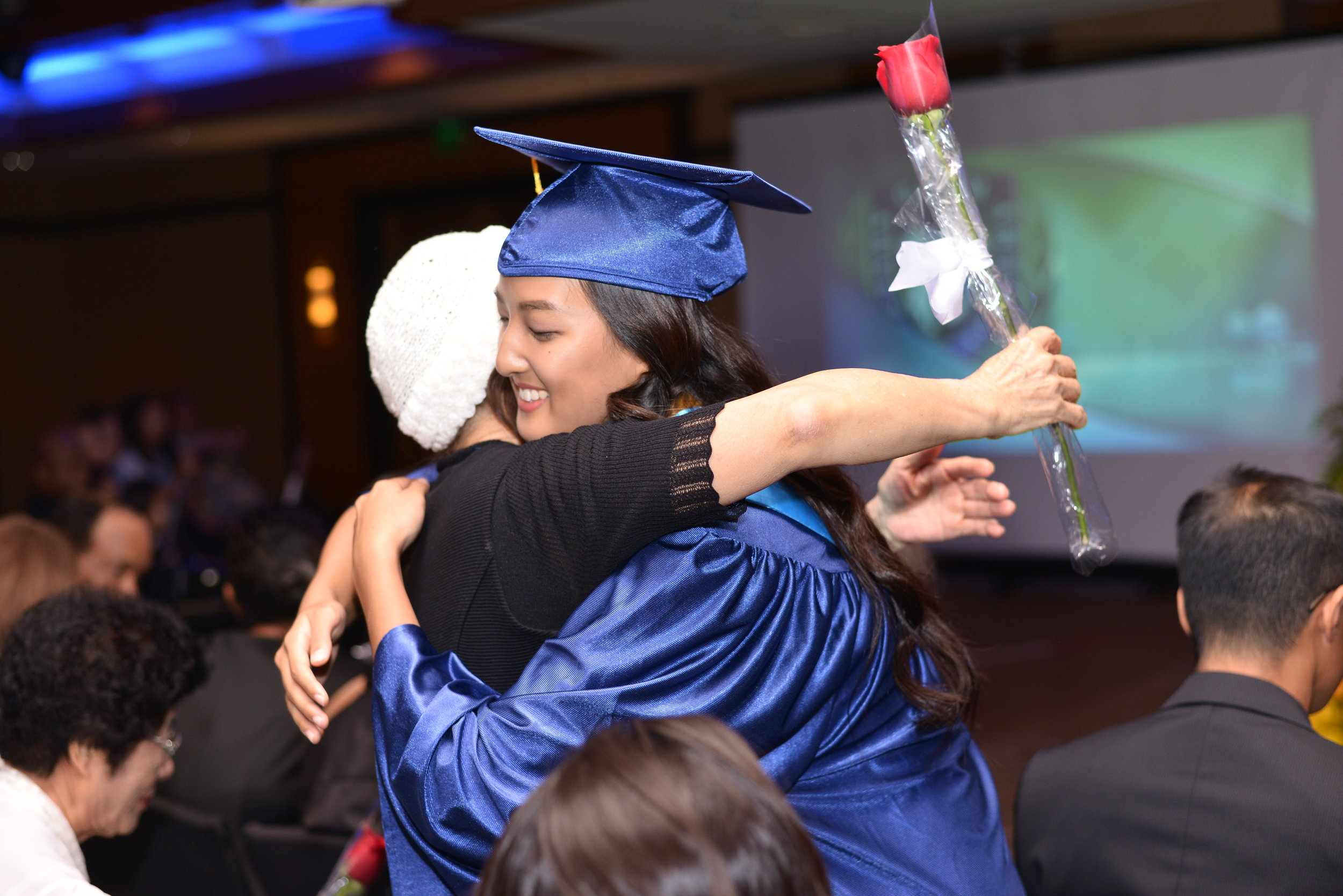 The graduates showed their appreciation to their family members by giving them roses.