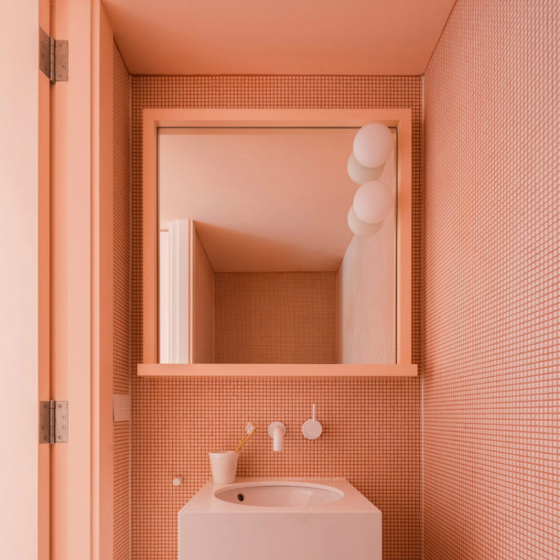 Tribe Studio    applied coral pink to the tiled walls, under-sink storage cabinet, and mirror frame of this bathroom in a Sydney home.