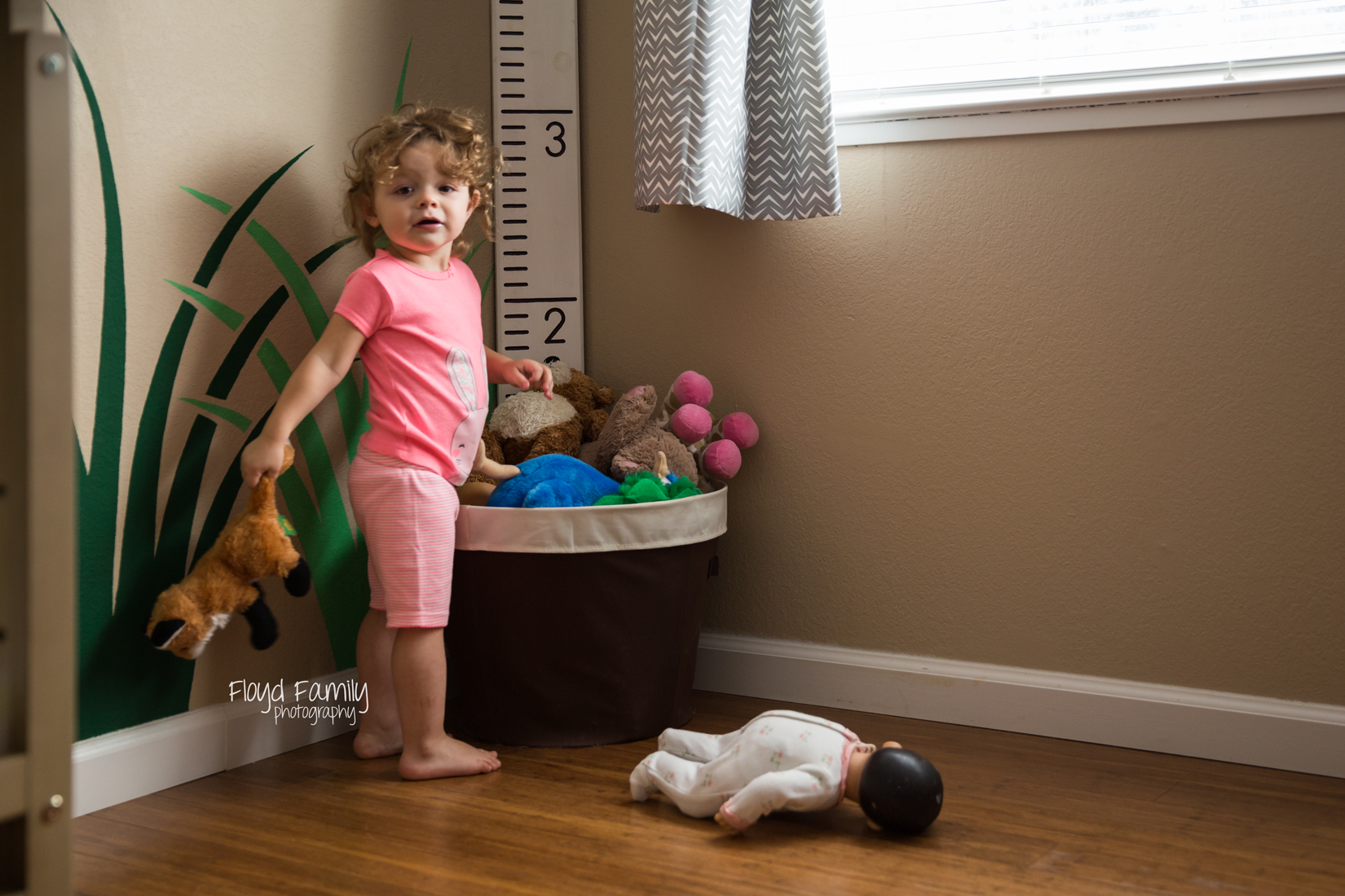Little girl playing with stuffed toys in the toy bin