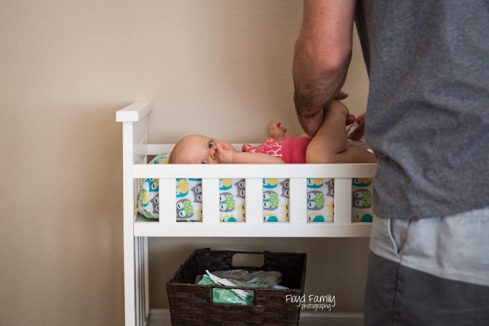 Dad changing baby's diaper at changing table