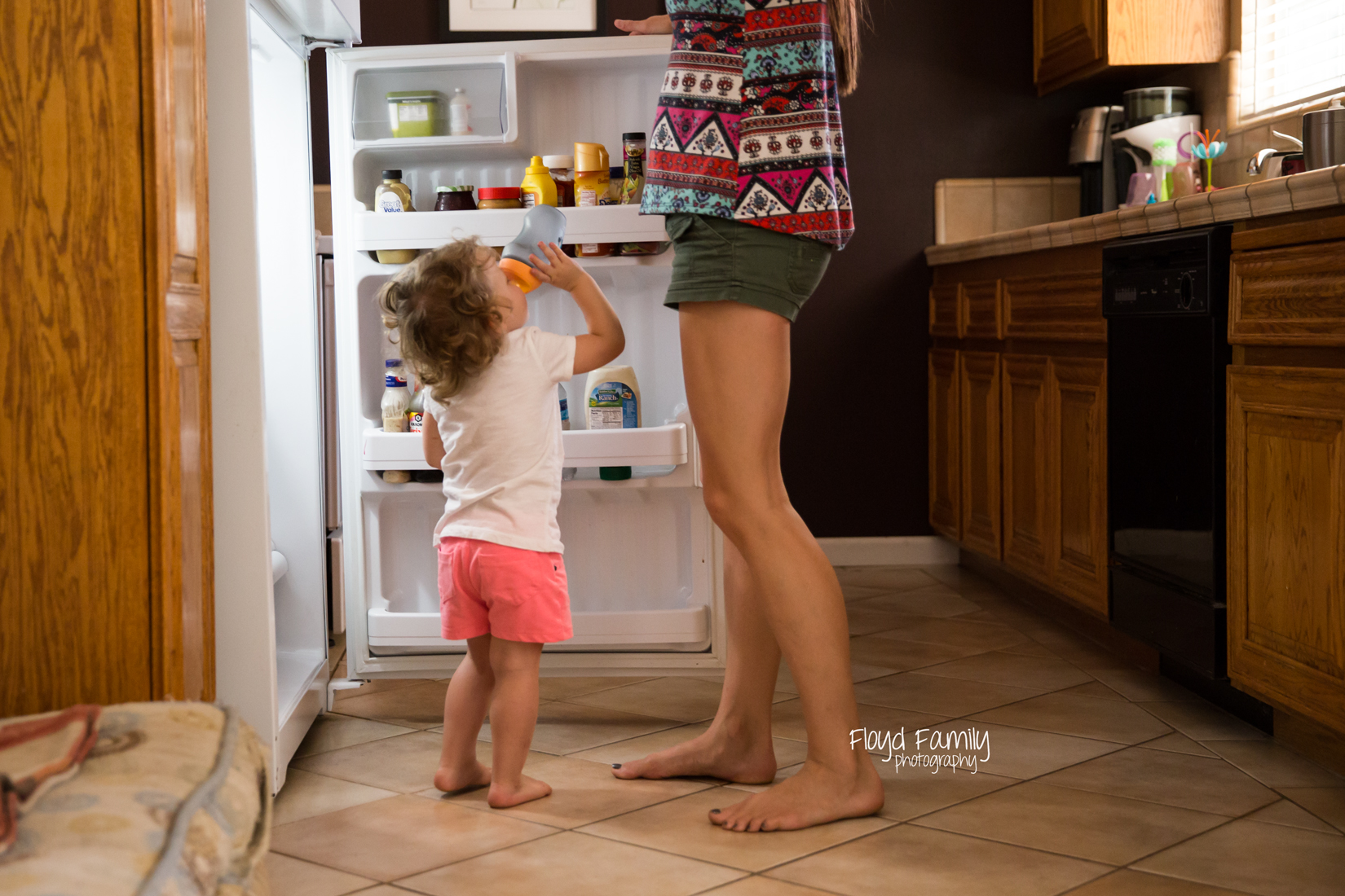 Little girl standing at open fridge with mom drinking milk