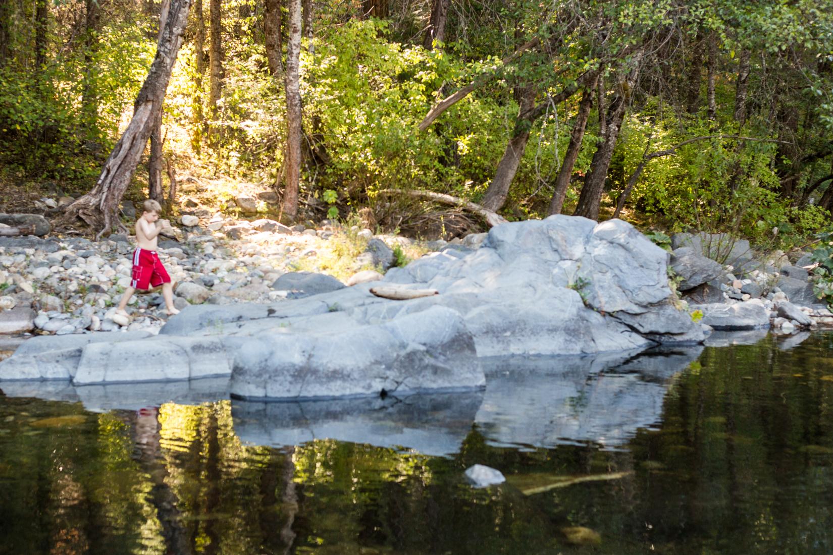 Boy walking along rocks around river | Placerville-Children-Photographer
