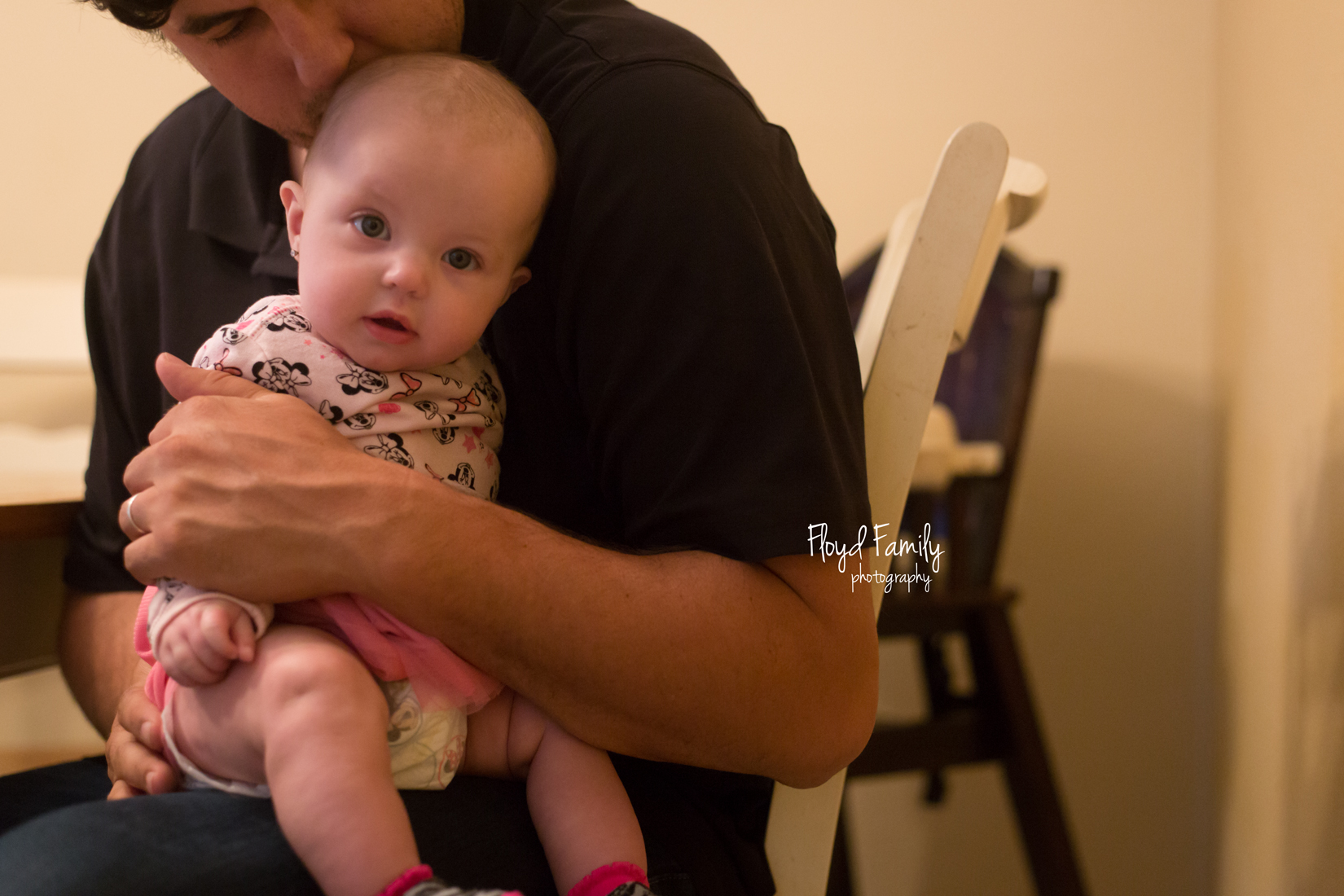 daddy holding baby in lap while sitting down