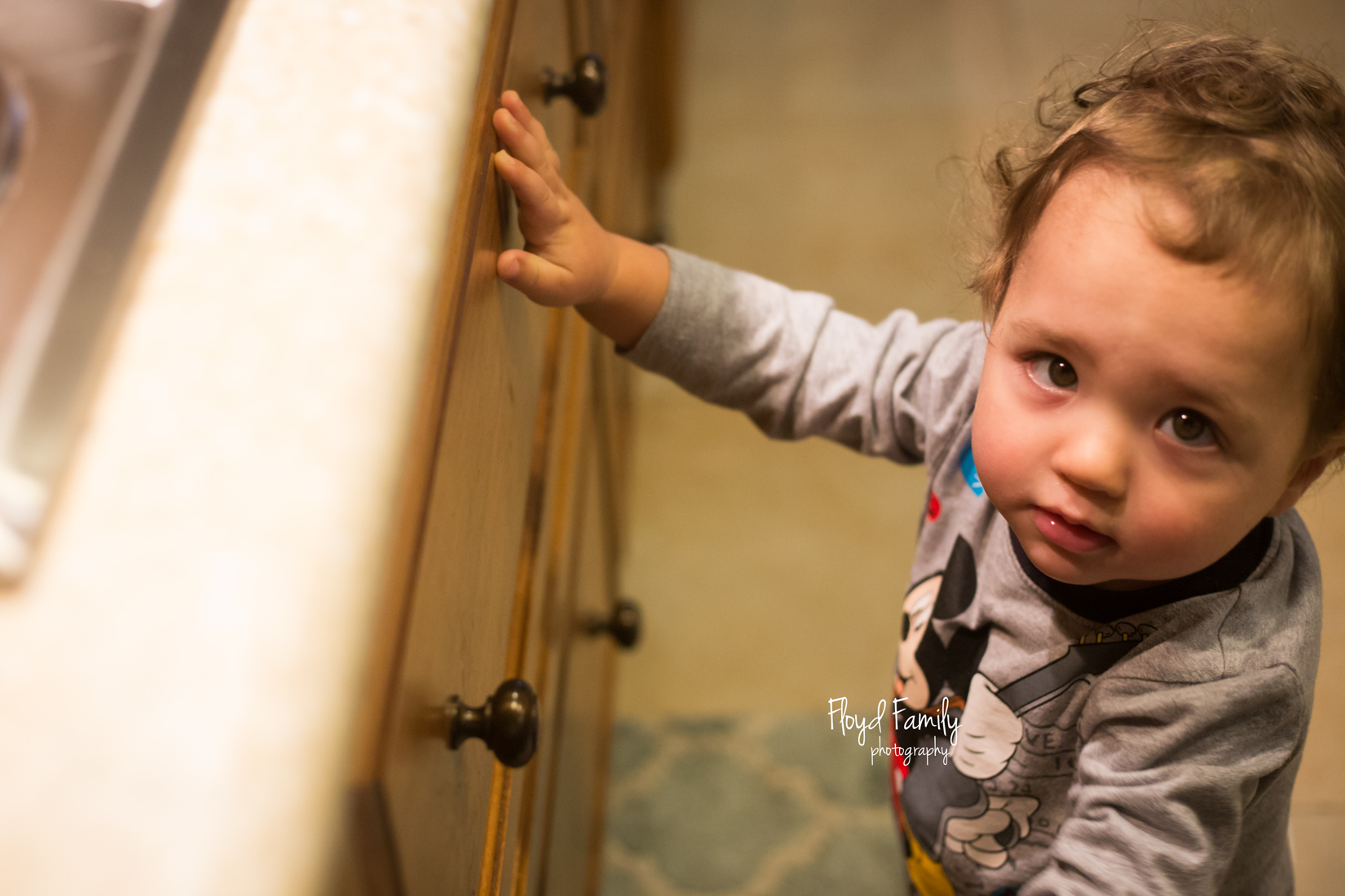 toddler looking up at camera while in the kitchen