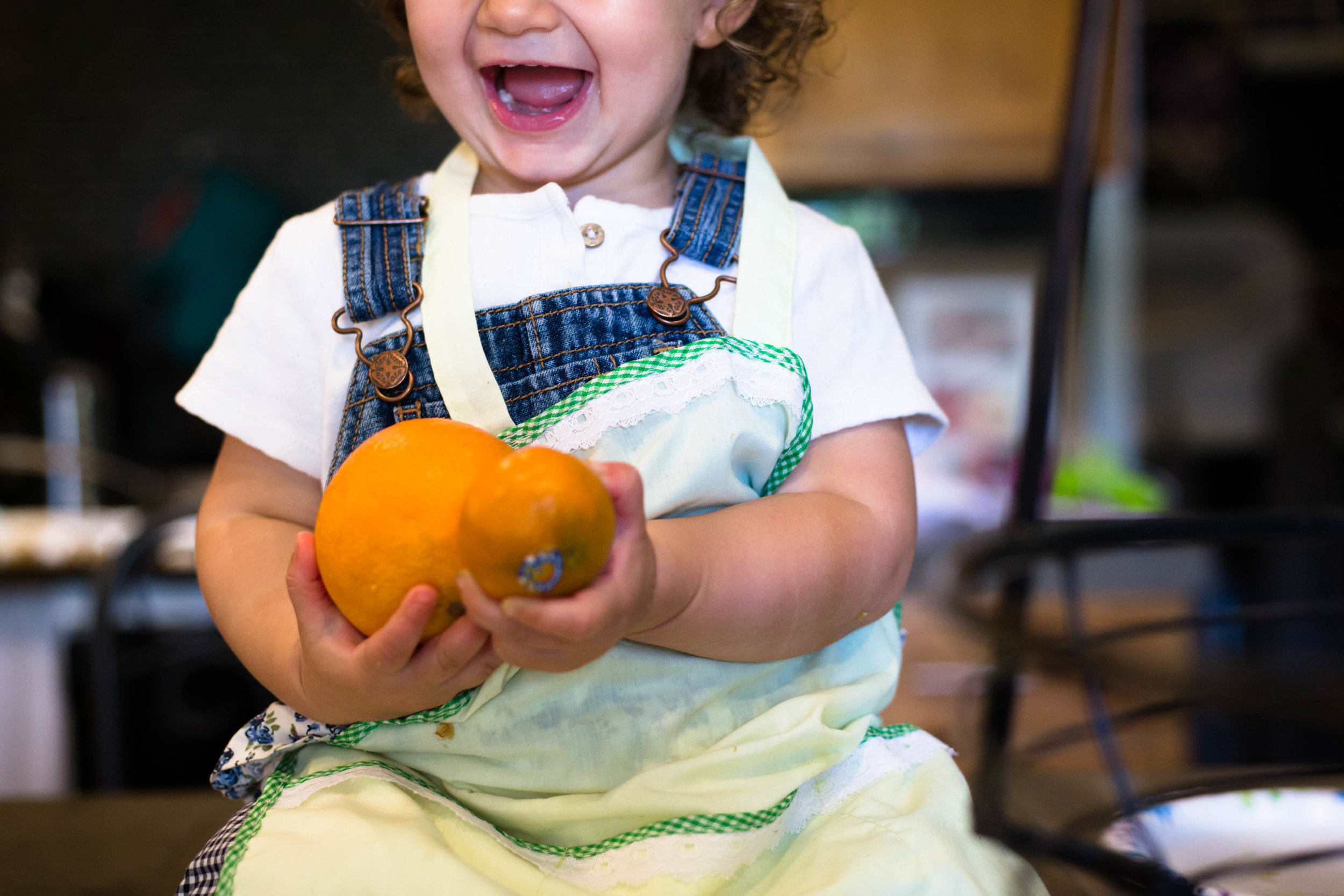 Little girl laughing holding oranges on the counter in her home