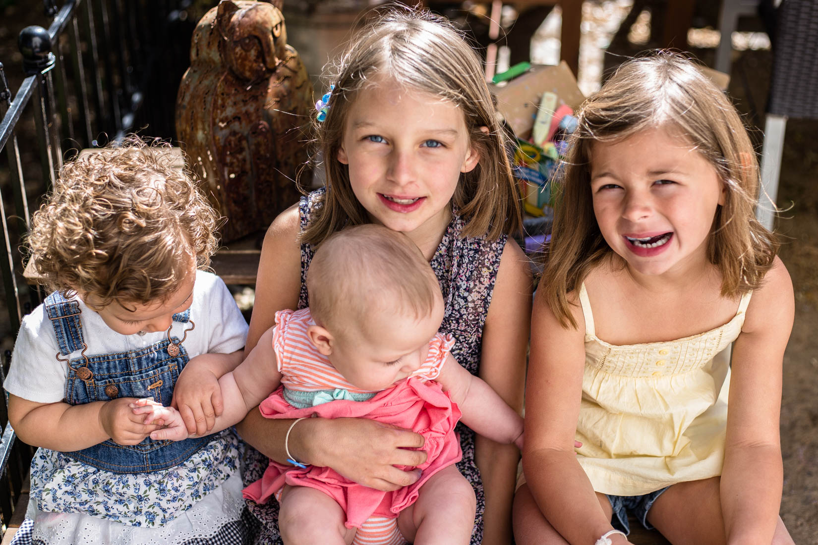 Four young girls smiling/not smiling at the camera sitting on a table | El Dorado Hills Photographer Family
