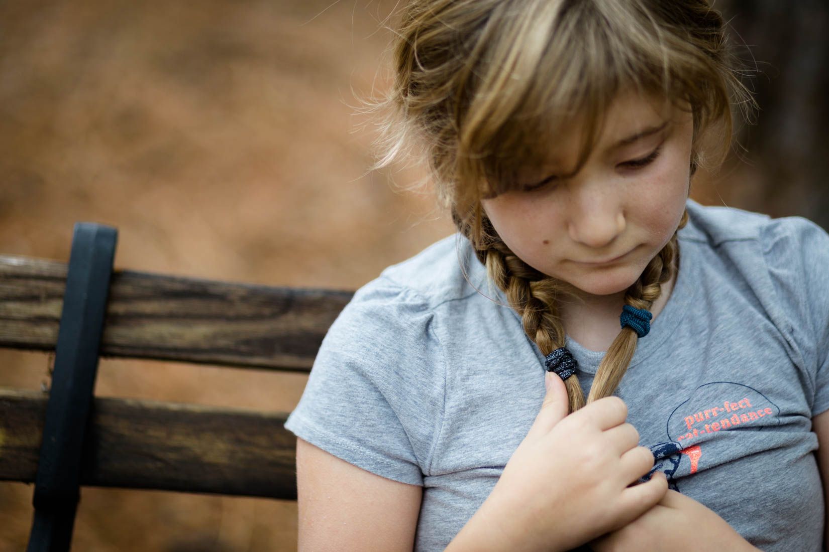 Little girl sitting on a bench playing with her pigtail braids with her hands while looking down