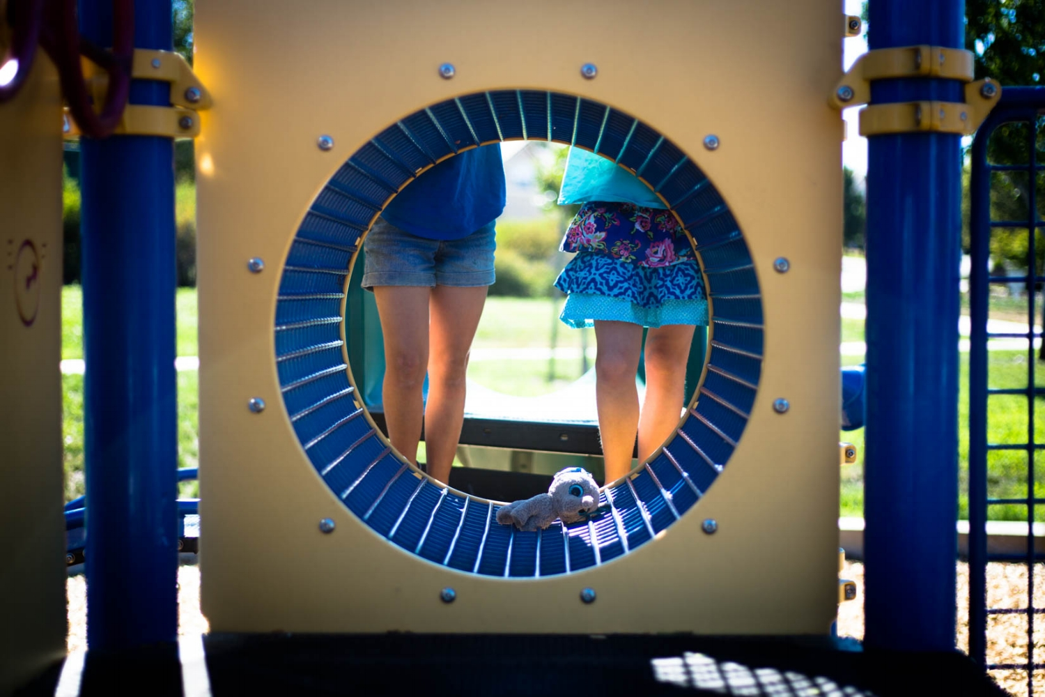 two girls standing behind the tunnel at the park with their stuffed animal wearing bright colorful clothes