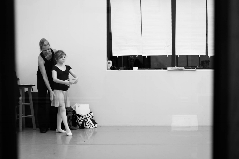 Girl dancing with teacher in ballet class