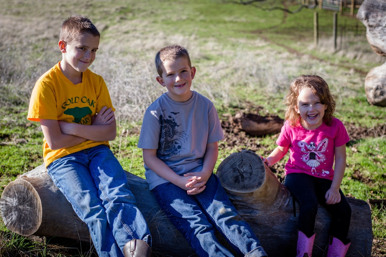 Three kids sitting on a log smiling