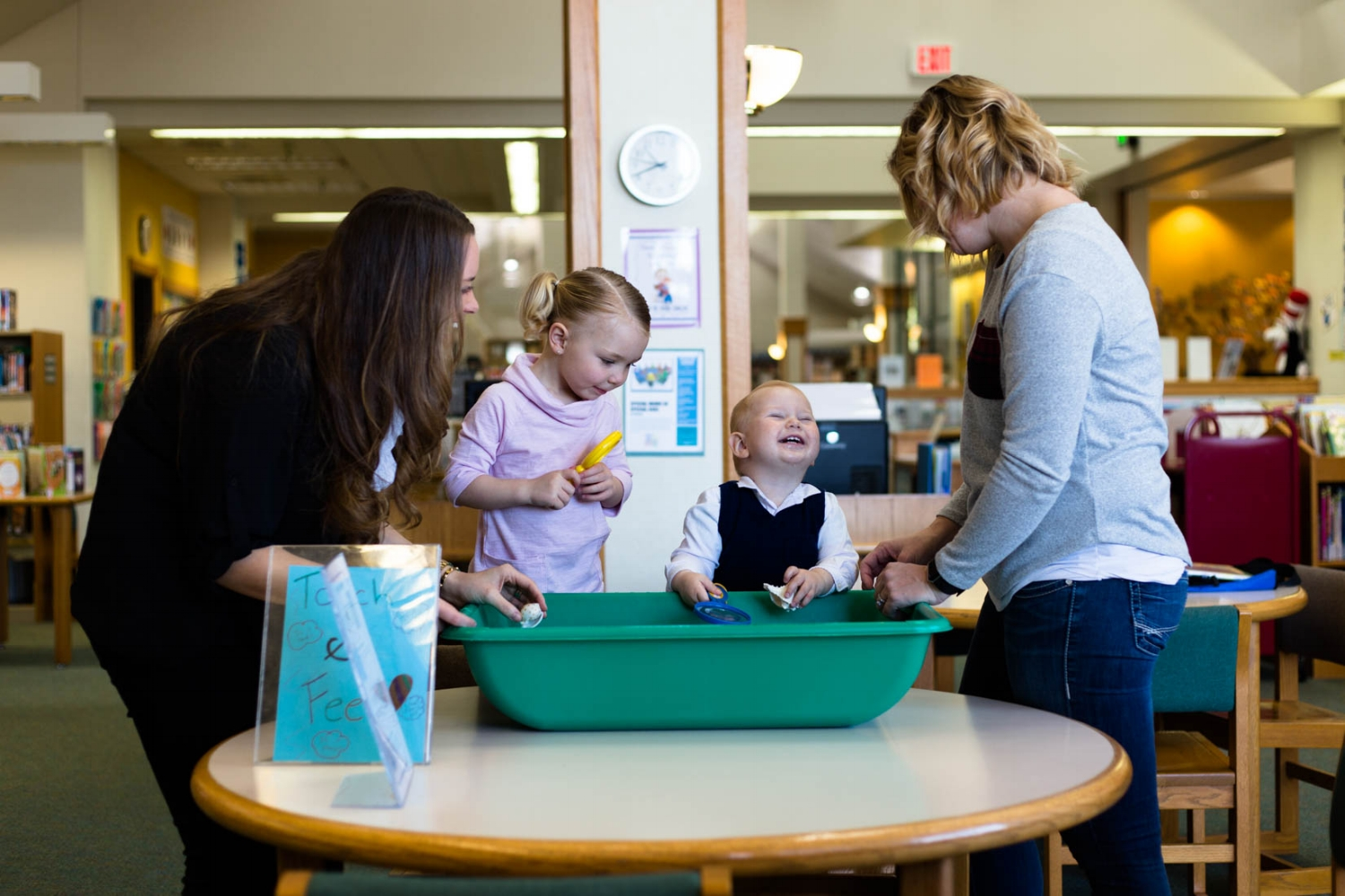 Two small children with moms at the see and touch table at the Cameron Park Library | El Dorado Hills Portraits Everyday