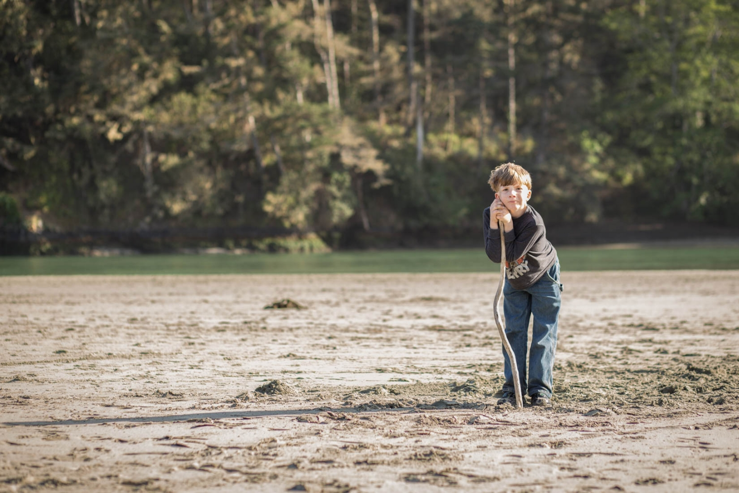 Picture of a boy standing with a large walking stick at the outlet of the ocean | Family El Dorado Hills Photographs
