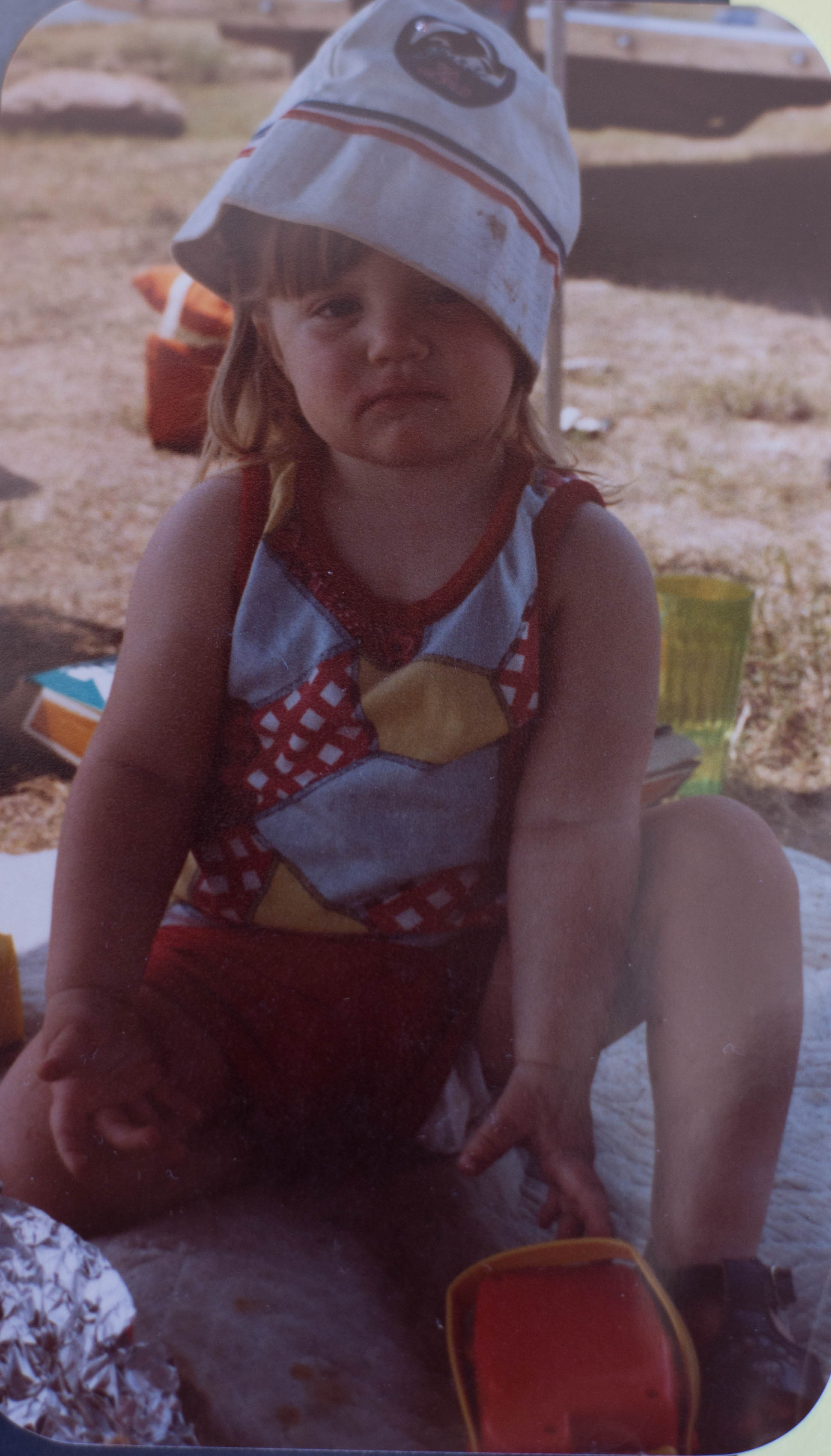 Little girl sitting on blanket for a picnic wearing a lopsided hat