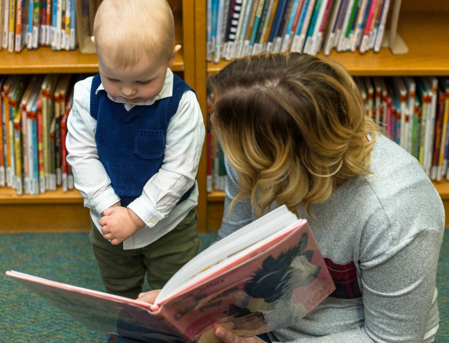 Little boy toddler standing listening to book being read at the library