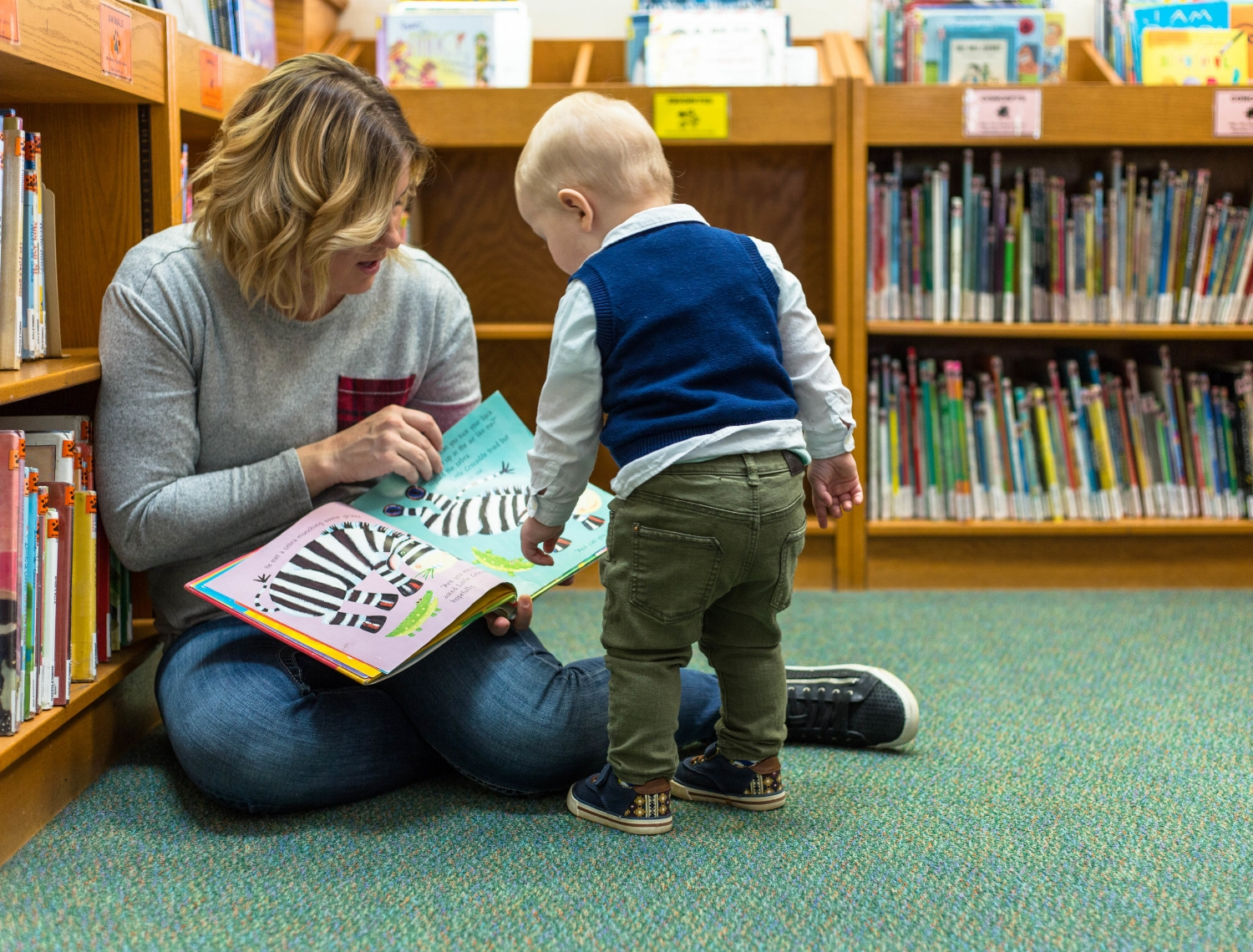 Little boy toddler helping read book at the library