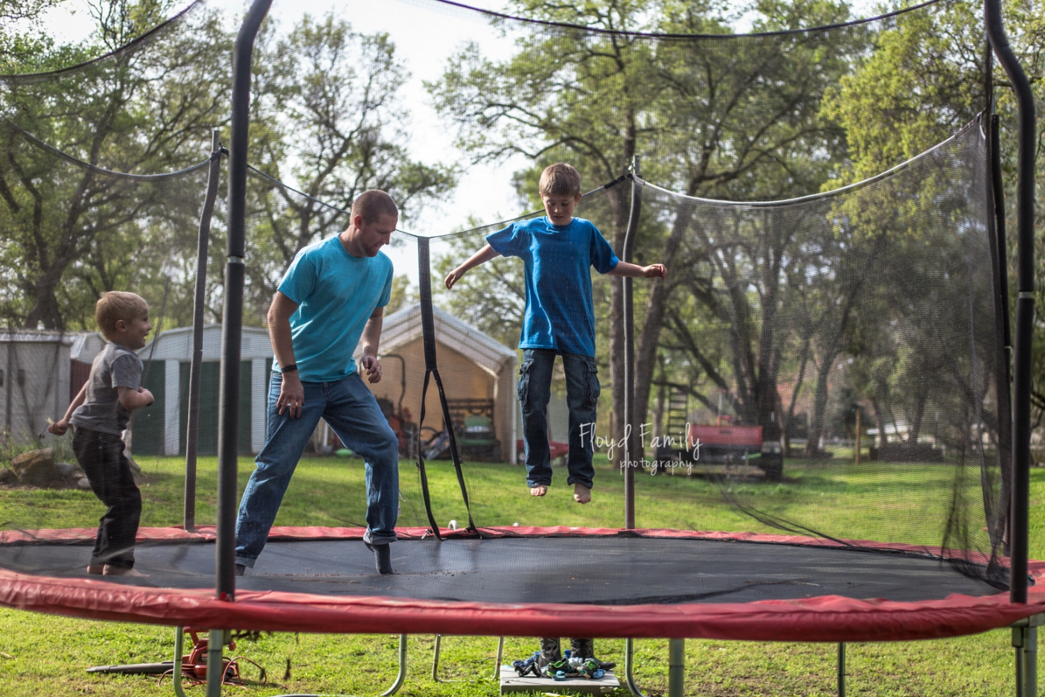 Two boys jumping really high with dad on the trampoline
