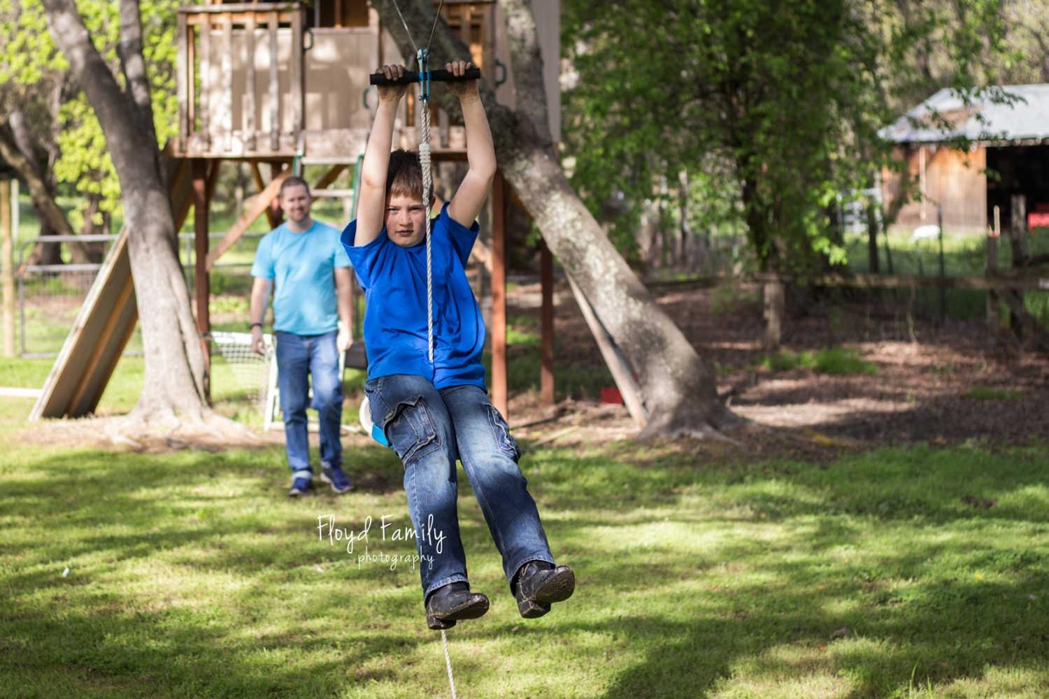 Boys swinging on the zip line in their back yard