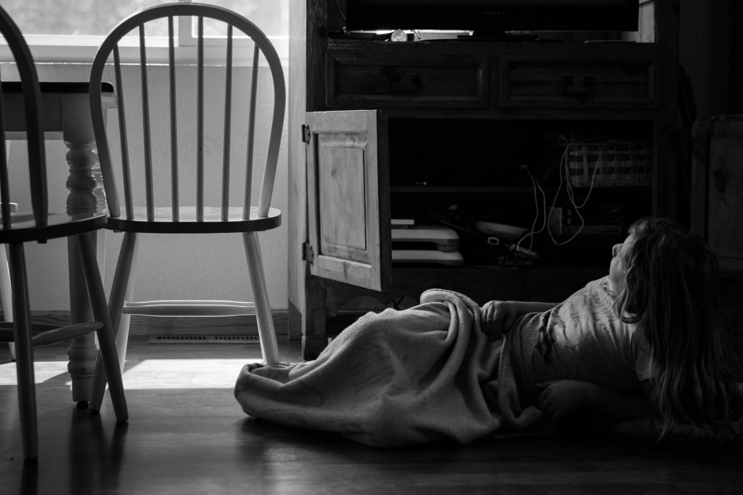 girl watching TV from the floor by the dining room table