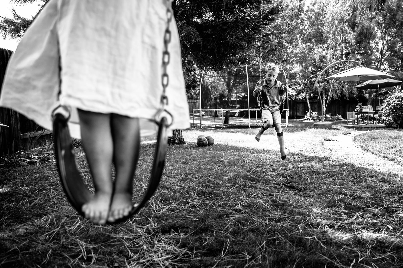 Two siblings swinging on the backyard swings having fun.