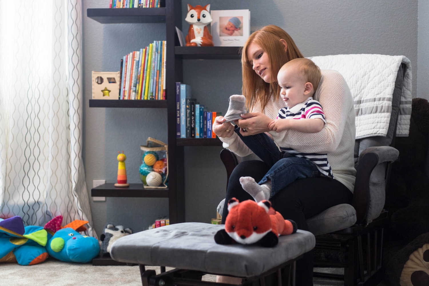 Mom putting on socks of two year old son sitting in a chair