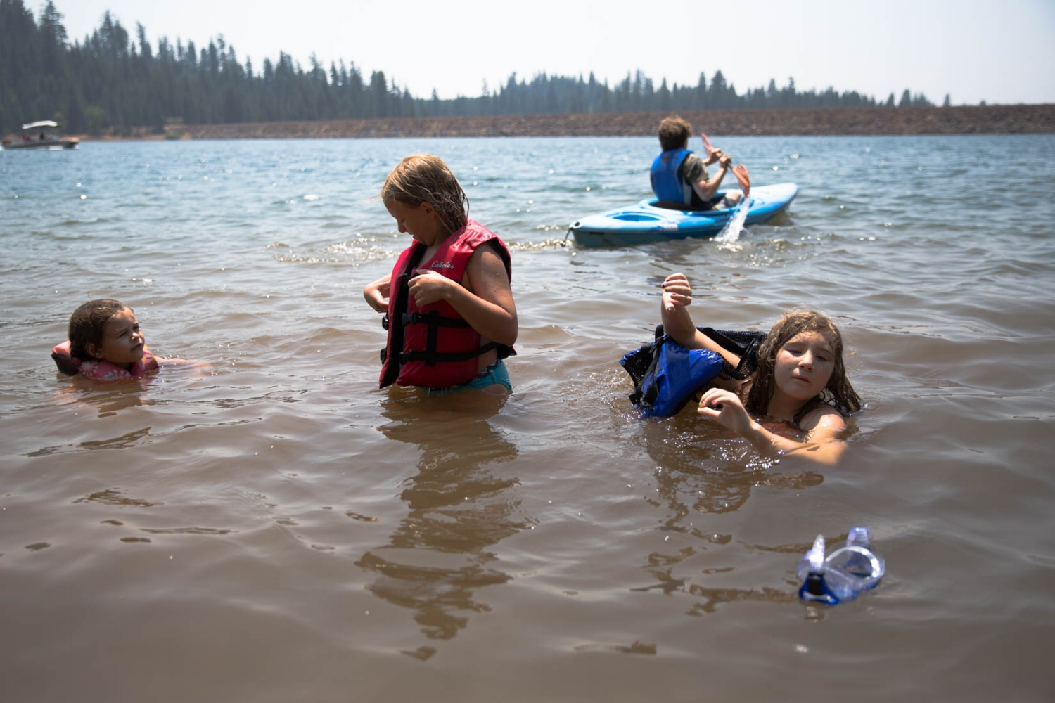 4 kids swimming in the lake with kayaks and life jackets Union Valley Reservoir