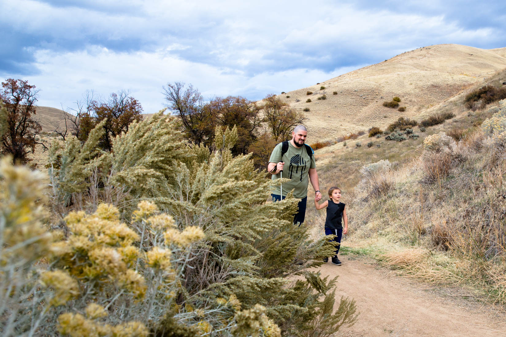 Dad and son walking on the hiking trails with the mountains ant the clouds behind them