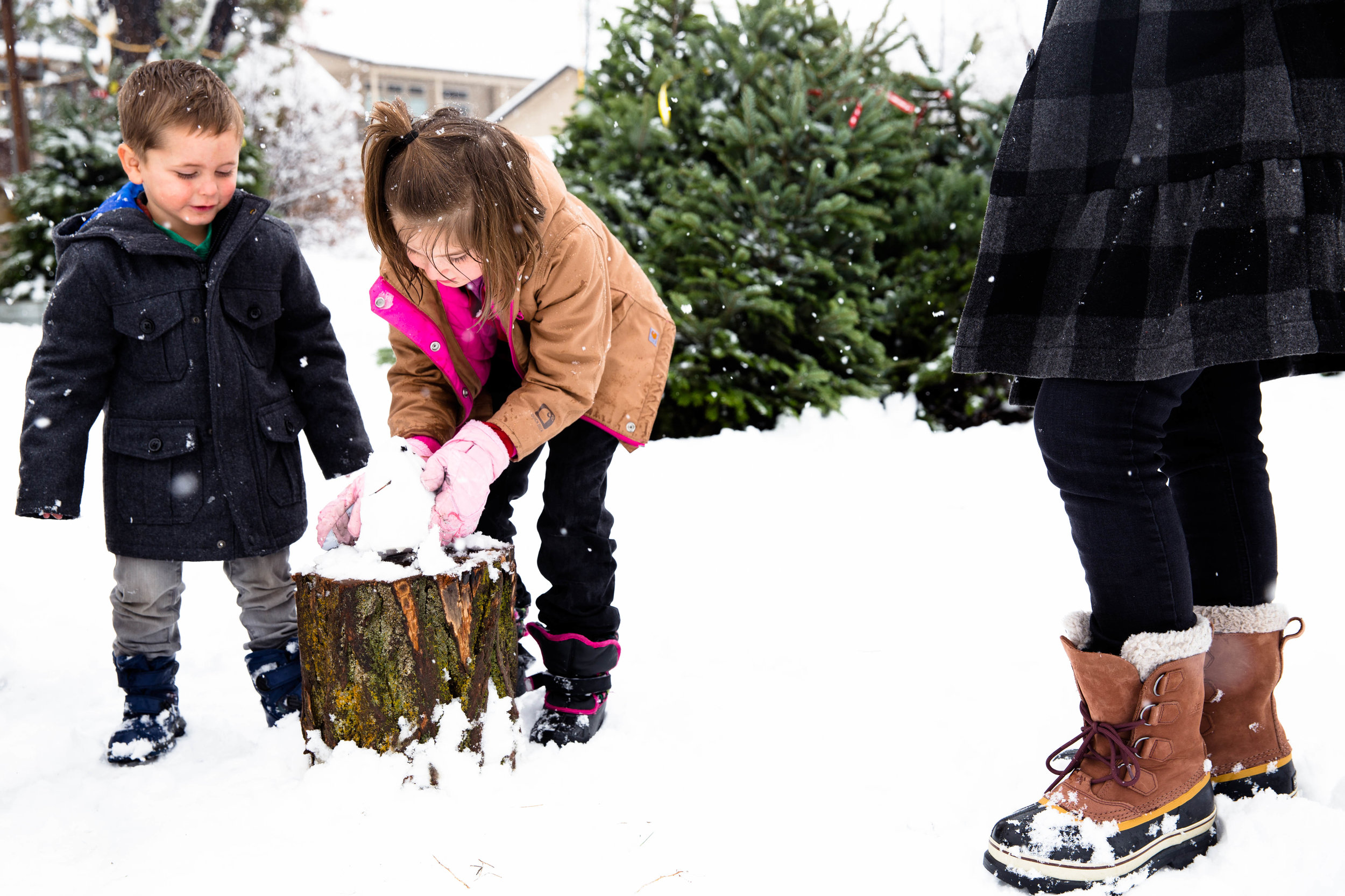 Building a tiny snowman in the snow while searching for the perfect Christmas Tree.