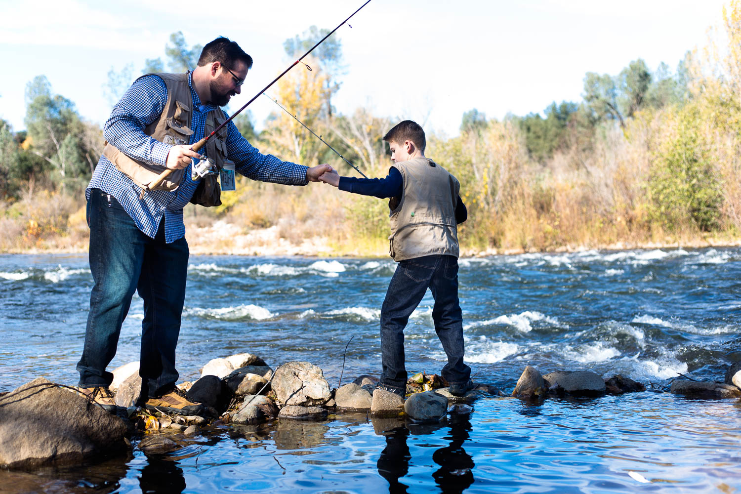 Dad and son fishing together holding hands crossing over river