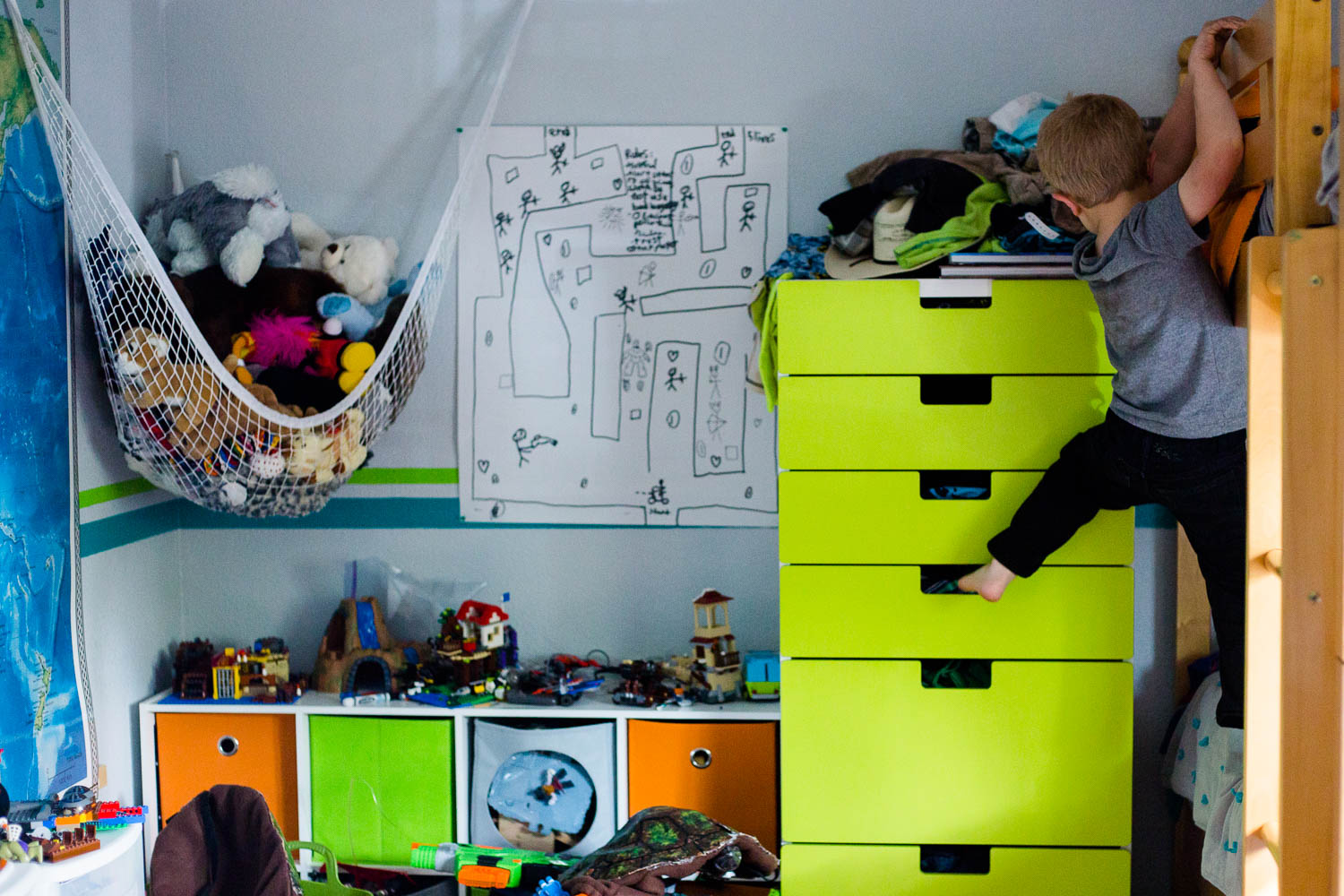 Boy climbing up bright green cabinet dresser to get onto top bunk bed