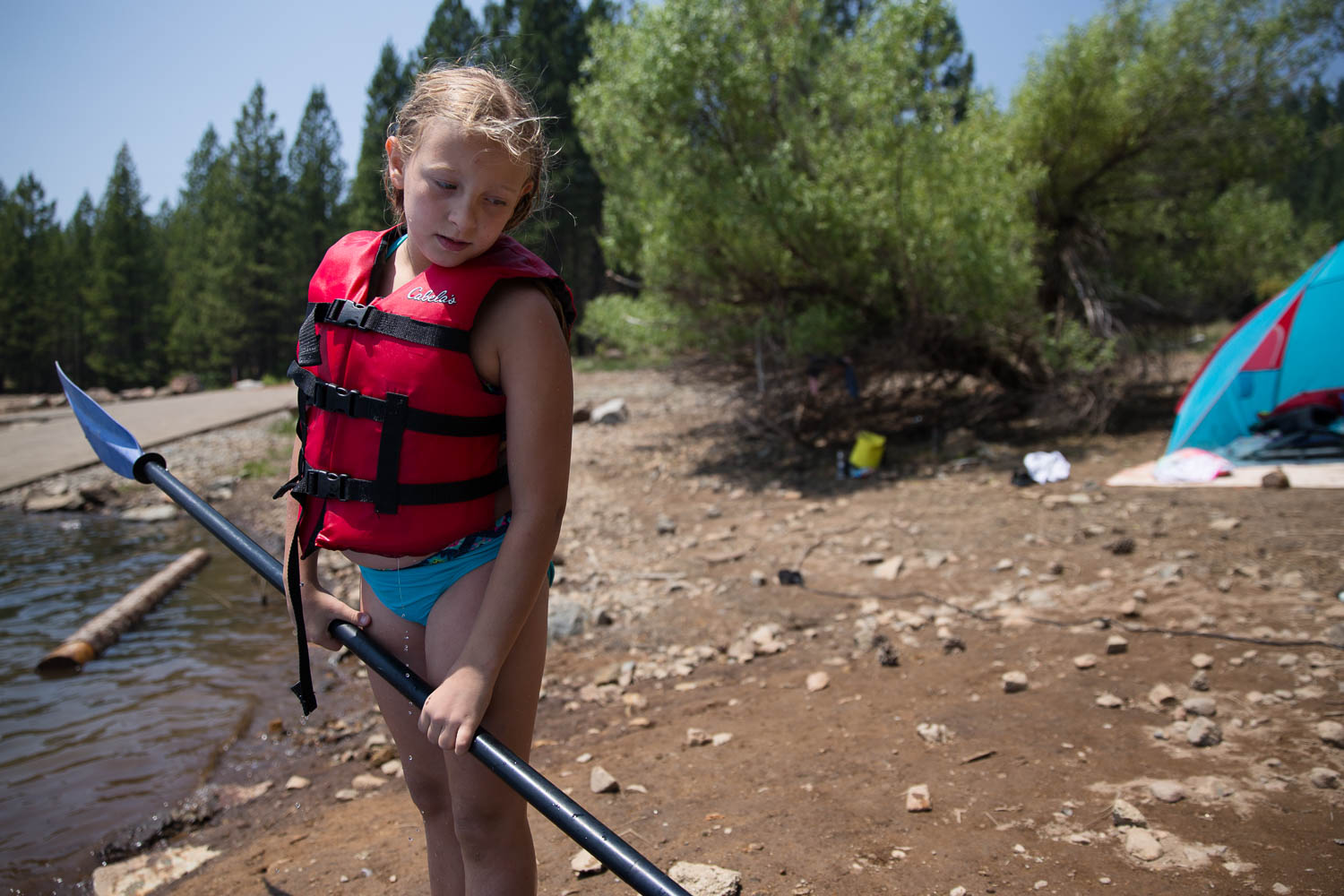 Young girl waiting to go into the water and kayak at the lake while family is camping.