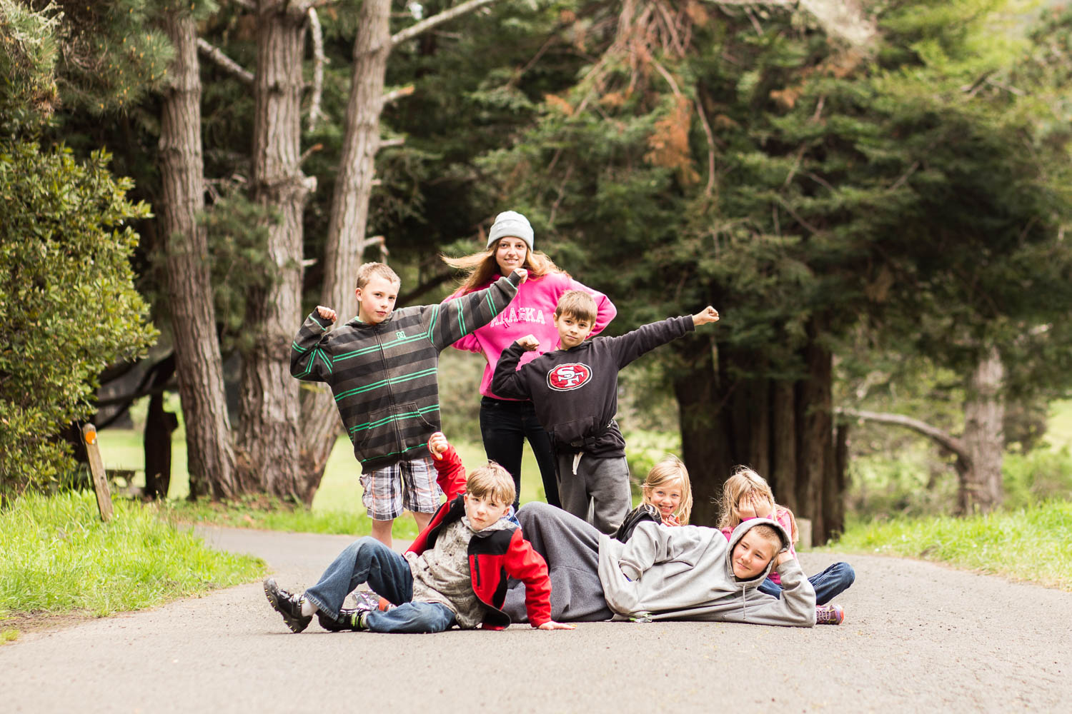 7 kids sitting in the middle of the road on a camping adventure posing for a picture