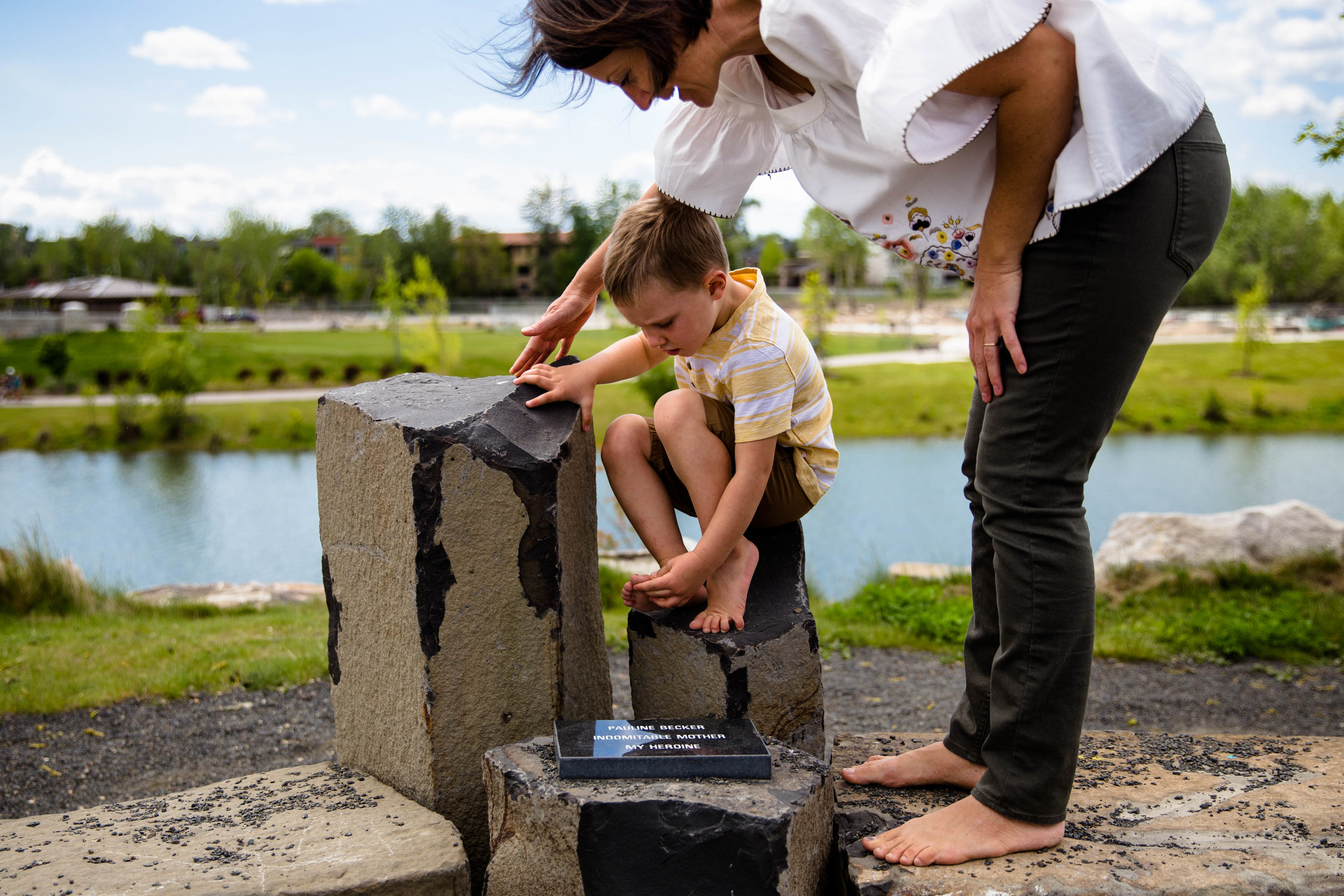 Mom looking down at son with smiles as he shows her his foot. Sitting in front of quinns pond. Esther simply park in boise Idaho.