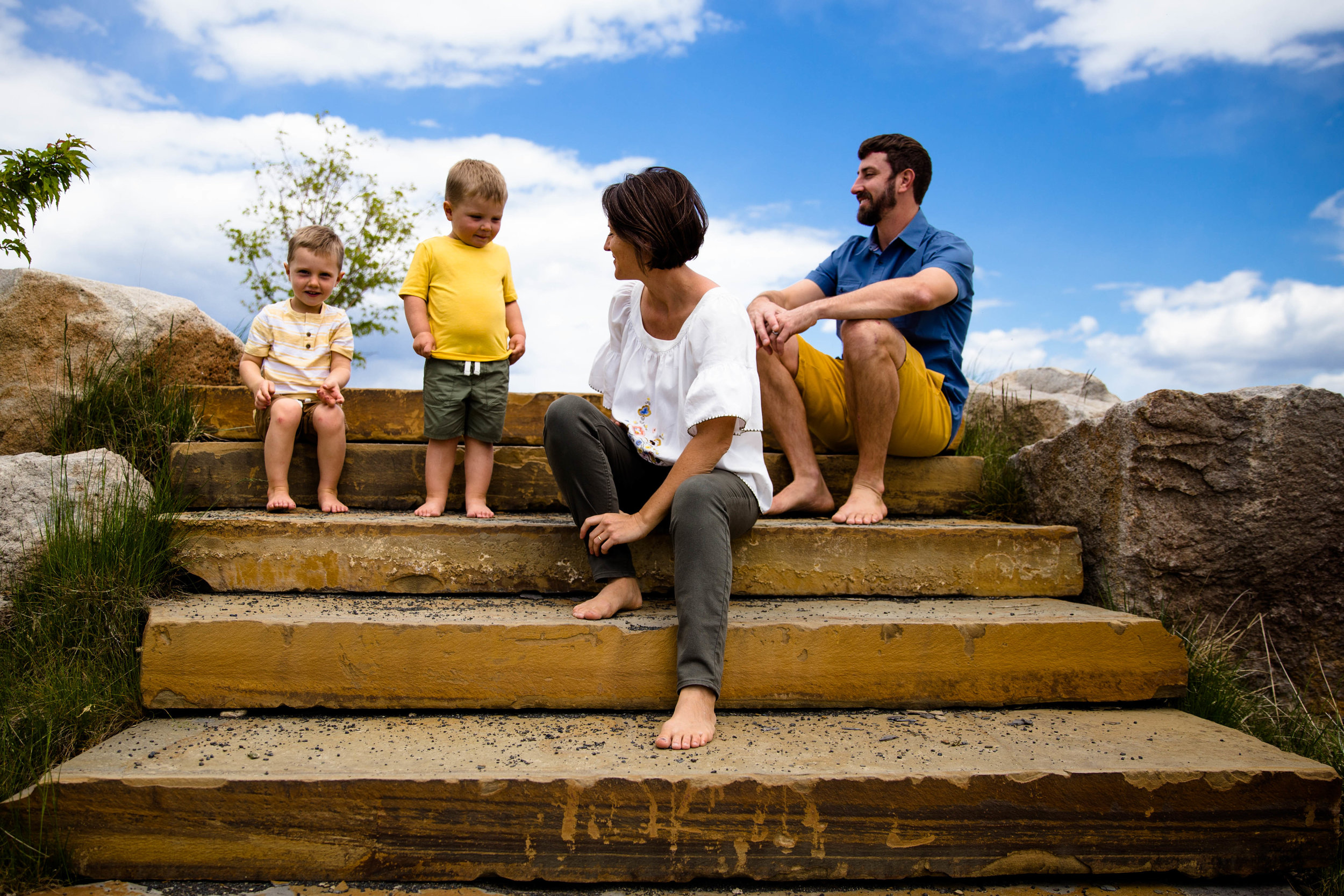 Family of four sitting on large granite steps in Esther Simplot Park/Quinn's Pond in Boise Idaho. Bright blue sky whit puffy white clouds int eh background. boy looking, dad laughing, mom smiling