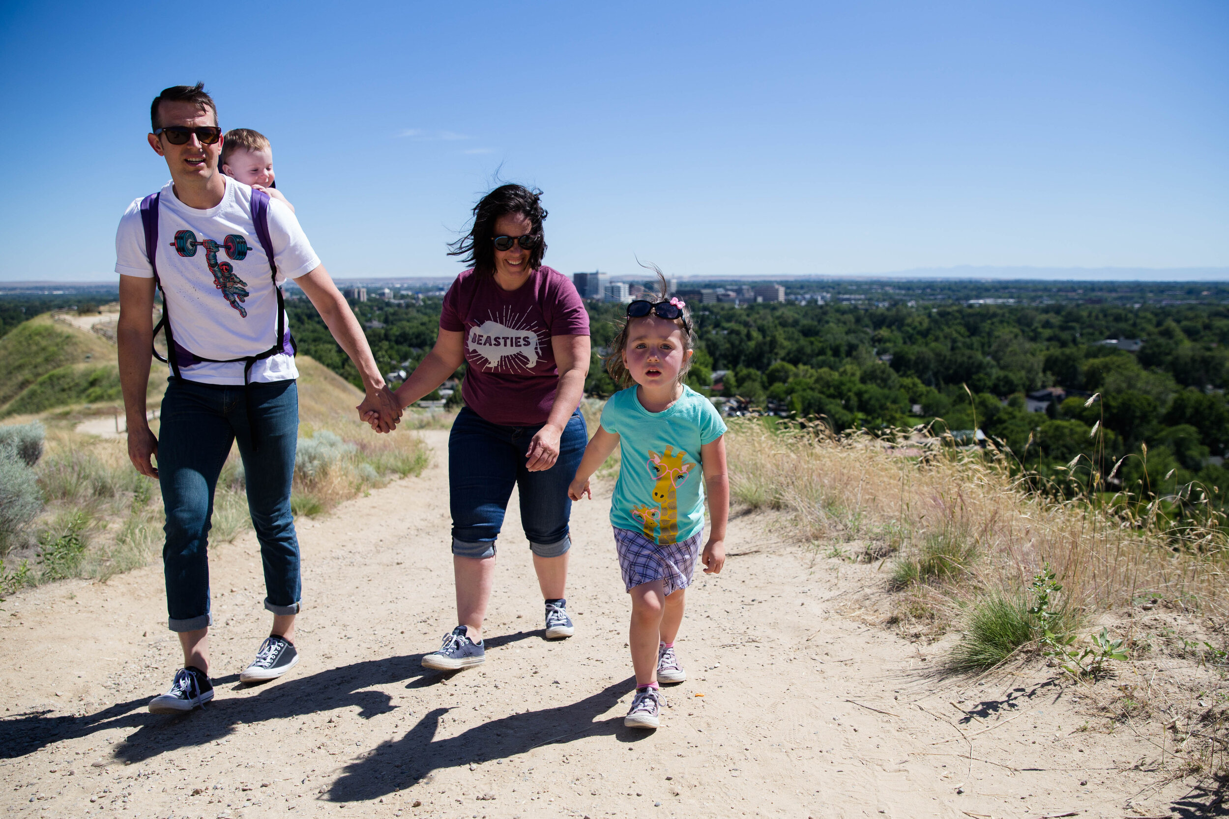 Family of four hiking up Camelsback trail in Boise. Overlooking city and the Boise State Capital behind them on a sunny day.