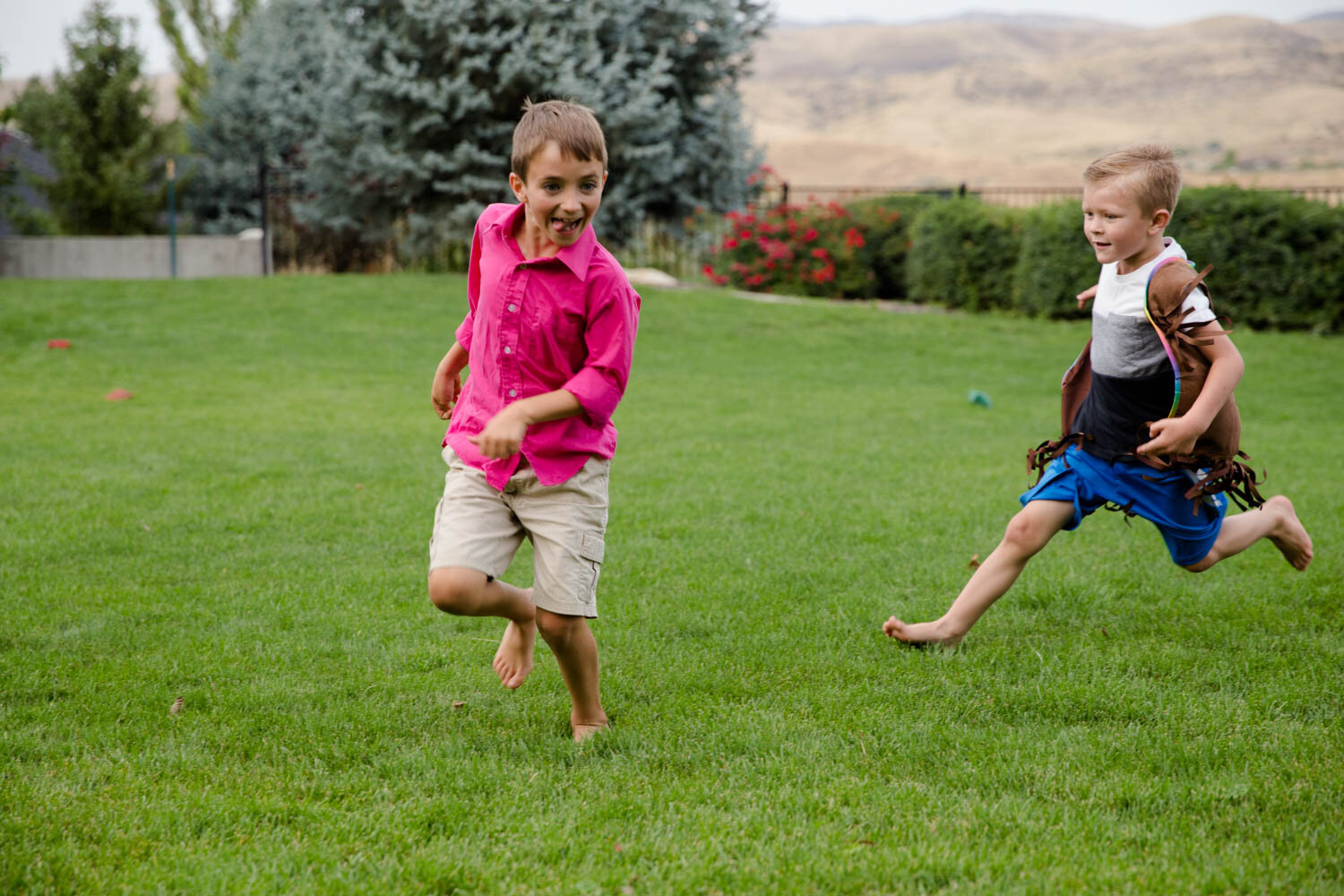 Two boys running and chasing each other and being goofy while in the backyard of a home in Hidden Springs near Boise Idaho.