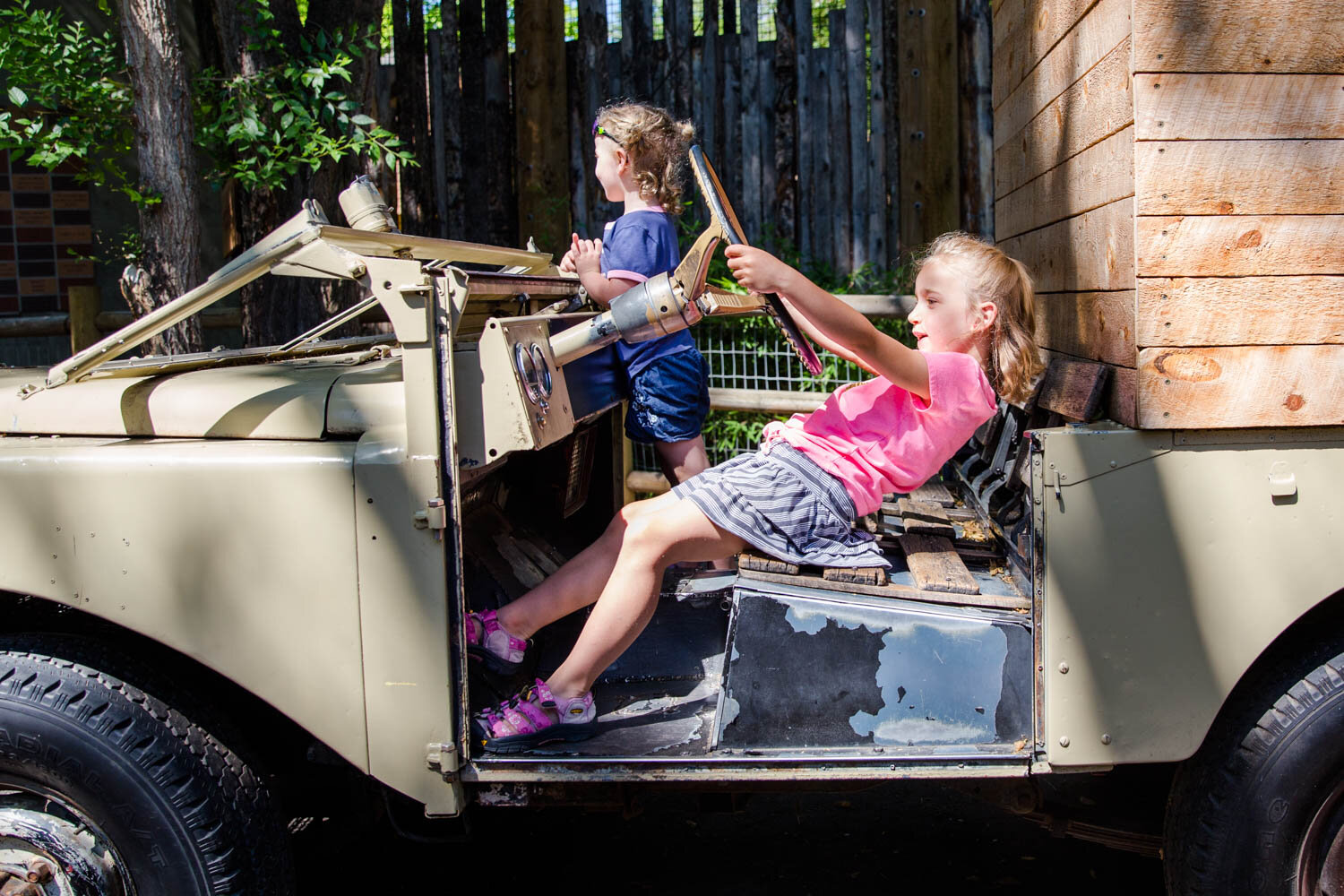 Two girls riding the jeep at Zoo boise for pretend.