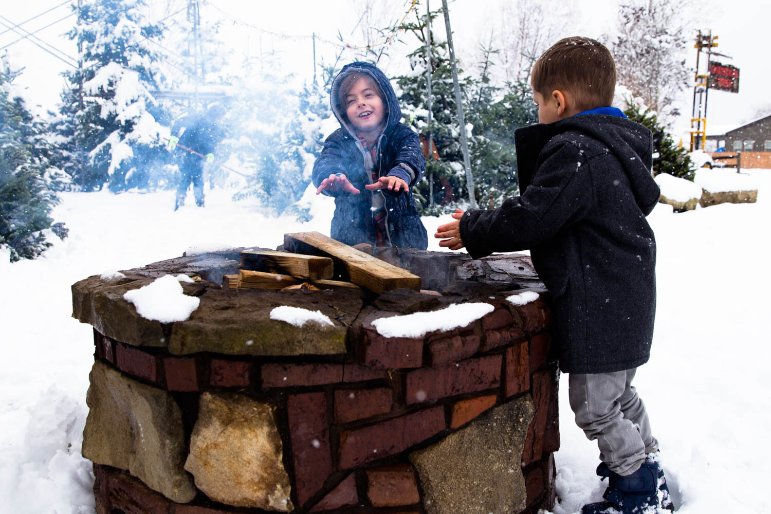Two kids sitting by the fire pit at the Christmas Tree lot in Boise ID warming their hands.
