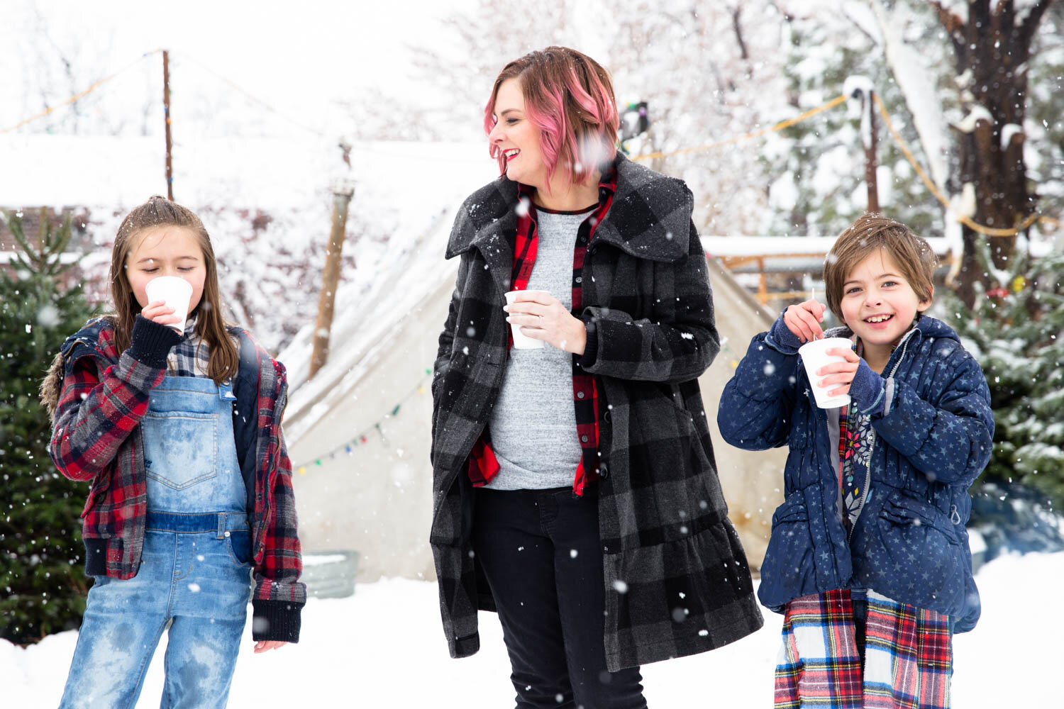 Mom and two daughters laughing and drinking hot chocolate while they search for their Christmas Tree at a lot in Boise Idaho
