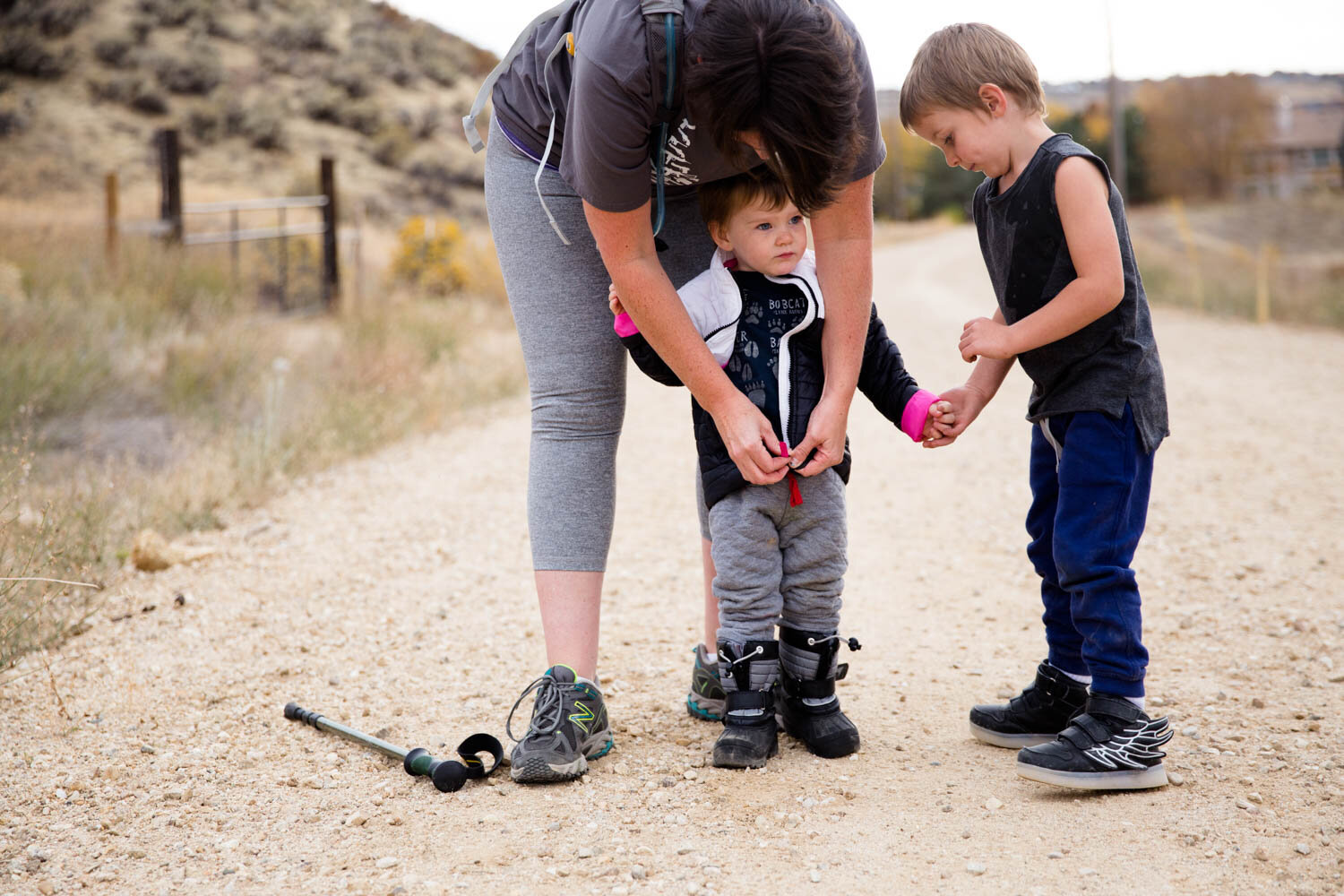 Mom helping daughter zipper up her coat as brother holds her hand on a hike in Boise.