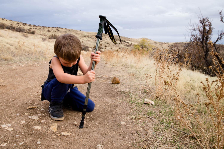 Little boy taking a kneel with his walking stick on hike in Boise Idaho