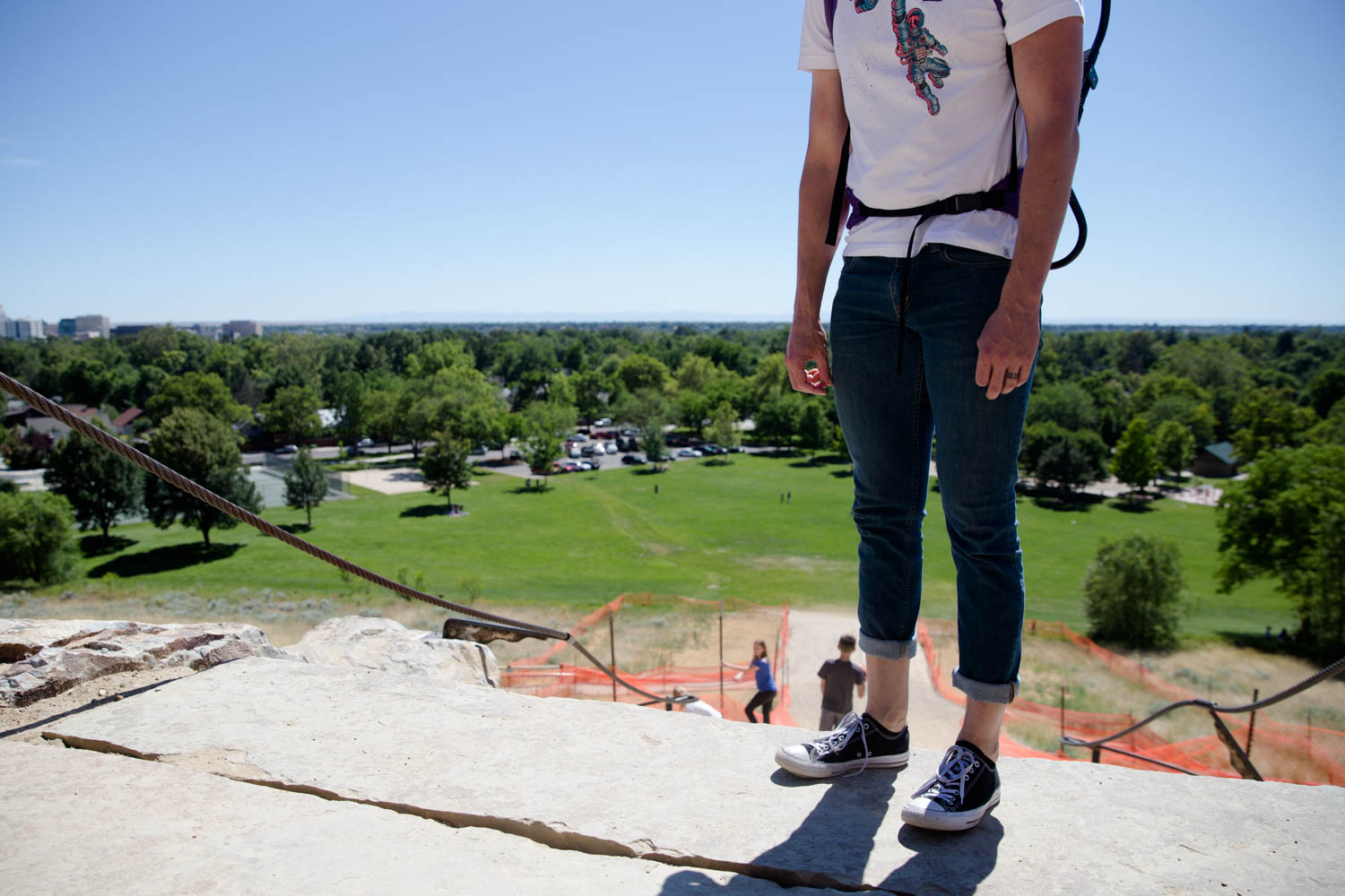 Dad standing at the top of the stairs at Camelsback Park in Boise ID. Converse shoes and short jeans carrying a kid on his backpack with hands down. Relaxed. Overlooking city.