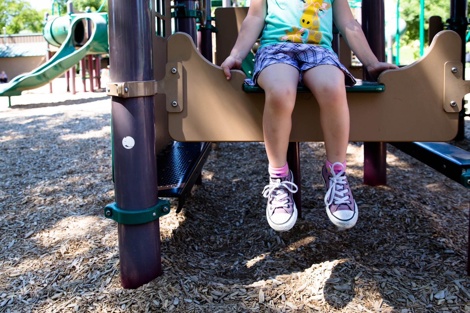 Small child sitting at the playground at camelback park boise Idaho. Hanging feet over the ledge.